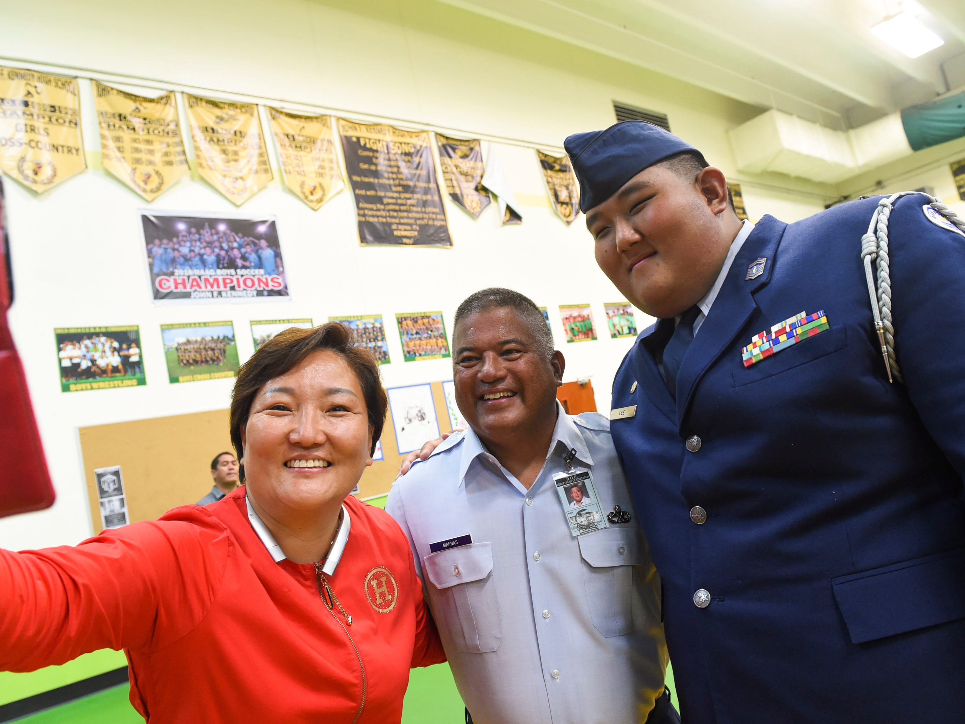 Ina Lee, left, Joseph A. Mafnas, John F. Kennedy High School Air Force Junior ROTC instructor, center, and Aaron Lee take a selfie at the JFK High School Gym, Nov. 9, 2018.