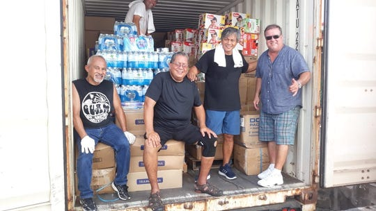 Ayuda Foundation board members  from left: Sen. James V. Espaldon, former senator Frank Blas Jr., Joe John Mantanona, and Walden Weilbacher take a break after helping sort, box, and load items received at the foundation's main CNMI typhoon donation collection and loading center. Another 40-foot container is nearly full of relief goods and ready to be shipped to the CNMI.