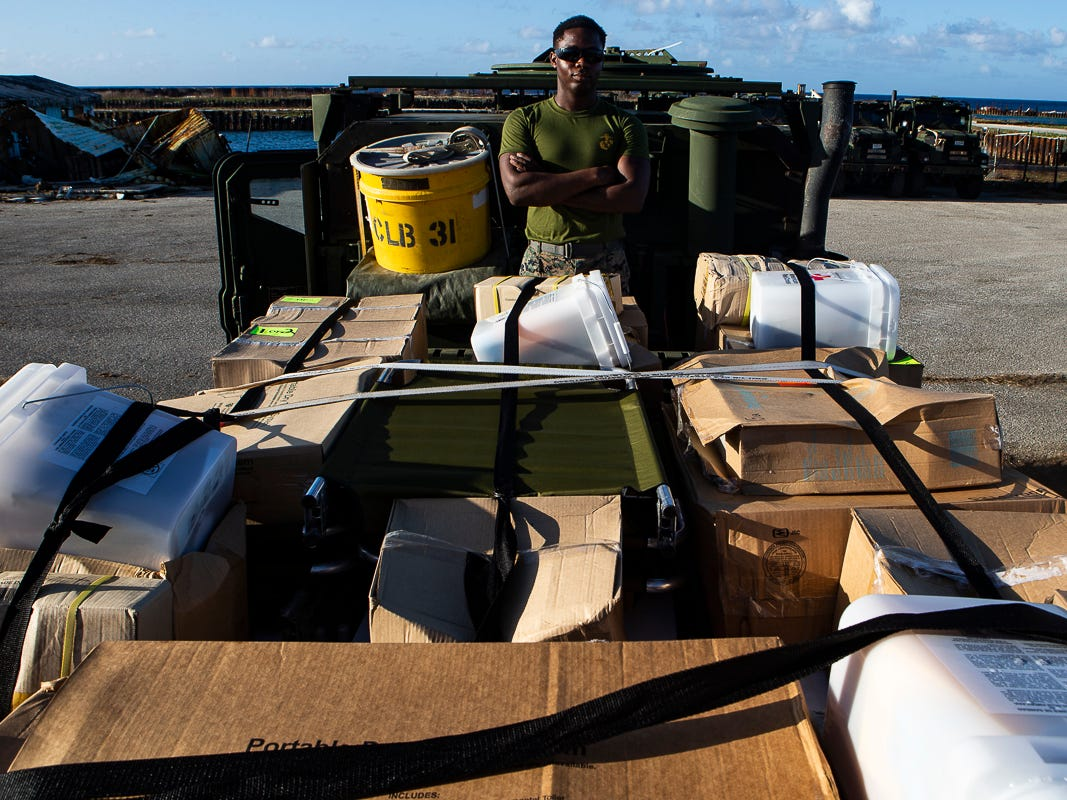 Lance Cpl. Franklin Dike, a motor transportation operator with Combat Logistics Battalion 31, stands atop a 7-ton flatbed truck packed with U.S. Federal Emergency Management Agency-provided emergency shelters for delivery to residents of Tinian, Commonwealth of the Northern Mariana Islands, Nov. 7, 2018. Dike, a native of Nigeria, immigrated to Chicago in 2015 before enlisting in the Marine Corps in 2017. Marines and Sailors with the 31st Marine Expeditionary Unit and CLB-31 arrived on Tinian Oct. 29-31 to lead relief efforts on Tinian in response to Super Typhoon Yutu as part of Task Force-West. TF-W is leading the Department of Defense's efforts to assist CNMI's local and civil authorities provide critical assistance for citizens devastated by Yutu, which struck Tinian and Saipan Oct. 25 as the second largest storm to ever hit U.S. soil. The 31st MEU, the Marine Corps' only continuously forward-deployed MEU, provides a flexible force ready to perform a wide-range of military operations across the Indo-Pacific region. (U.S. Marine Corps photo by Gunnery Sgt. T. T. Parish/Released)
