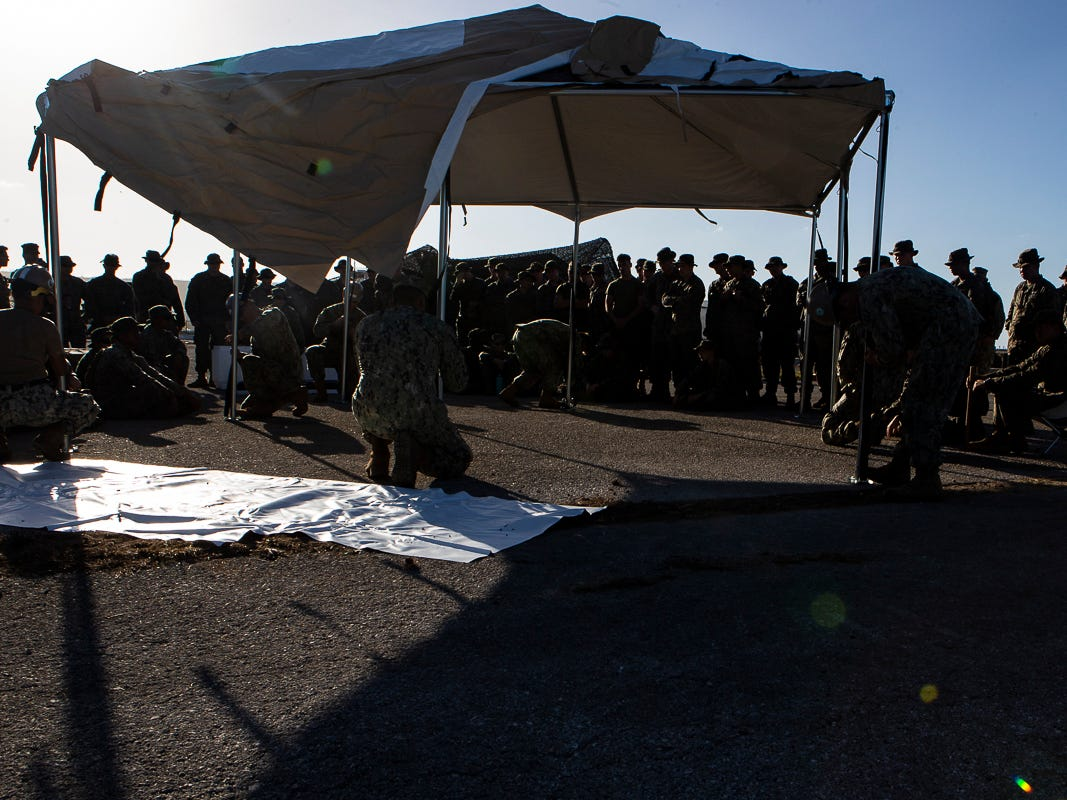 Seabees with Naval Mobile Construction Battalion 1 assemble a U.S. Federal Emergency Management Agency-provided emergency shelter as Marines with Combat Logistics Battalion 31 look on, Tinian, Commonwealth of the Northern Mariana Islands, Nov. 7, 2018. Marines and Sailors with the 31st Marine Expeditionary Unit and CLB-31 are assisting local and civil authorities on Tinian to deliver FEMA shelters for families affected by Super Typhoon Yutu, which struck here Oct. 25 as the second strongest storm to ever hit U.S. soil. Marines and Sailors with the 31st MEU and CLB-31 arrived on Tinian Oct. 29-31 to lead relief efforts on Tinian in response to Yutu as part of Task Force-West. TF-W is leading the Department of Defense's efforts to assist CNMI's local and civil authorities provide critical assistance for citizens devastated by Yutu. The 31st MEU, the Marine Corps' only continuously forward-deployed MEU, provides a flexible force ready to perform a wide-range of military operations across the Indo-Pacific region. (U.S. Marine Corps photo by Gunnery Sgt. T. T. Parish/Released)