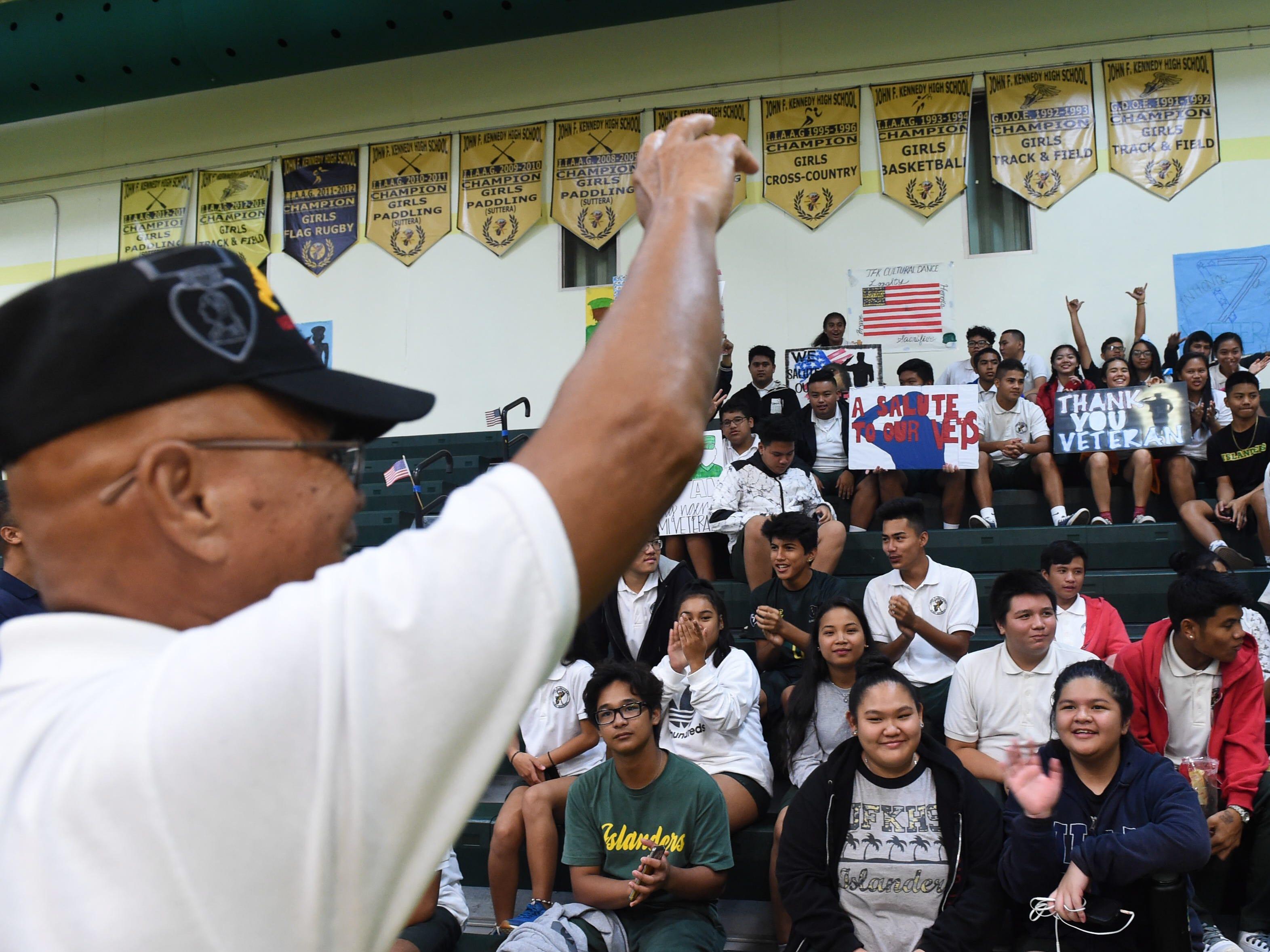 Guam veterans wave to John F. Kennedy High School students, Nov. 9, 2018.