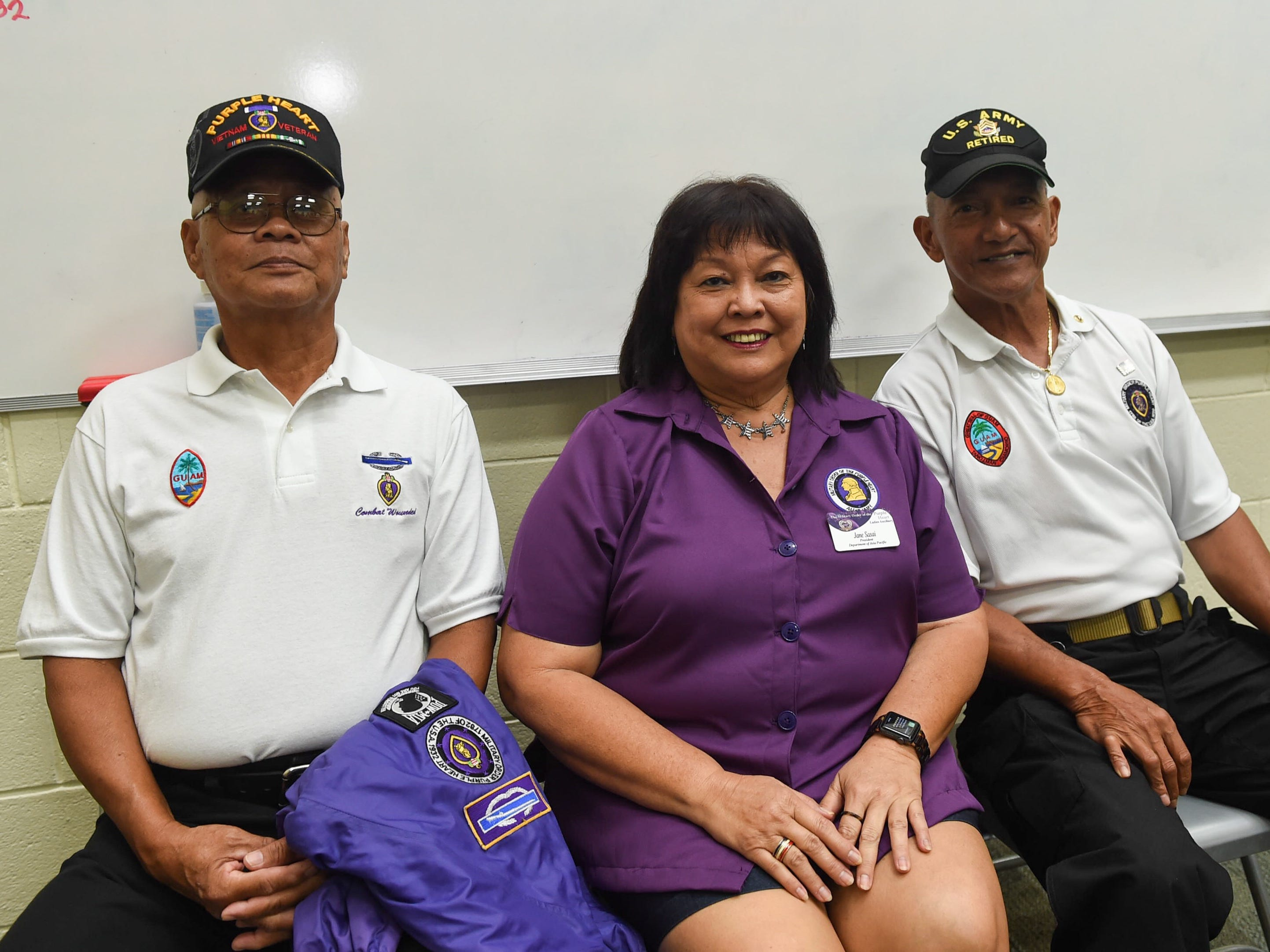 Veterans Thomas Mendiola, left, and Anthony Lukeala with Jane Sasai, Military Order of the Purple Heart Ladies Auxilary president, at John F. Kennedy High School, Nov. 9, 2018.