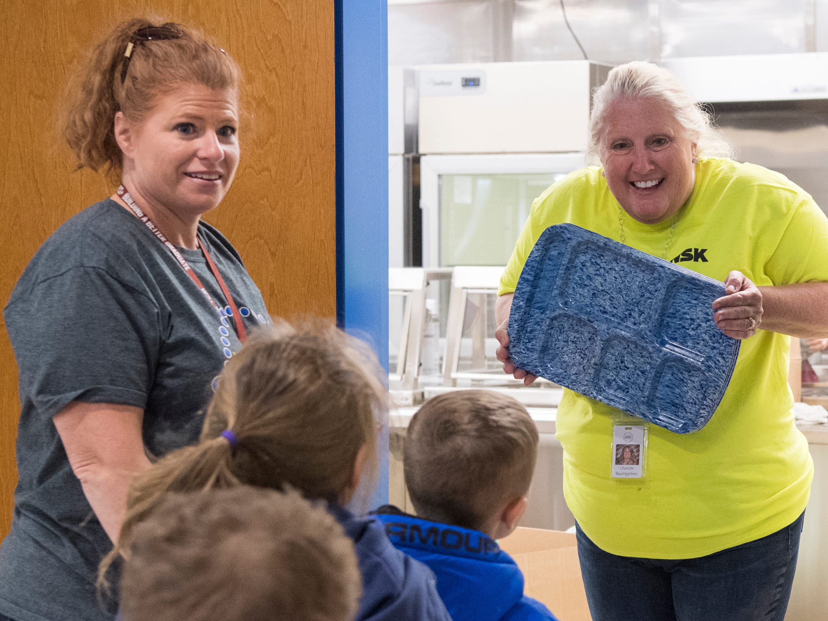 "Charlotte Baumgartner, Director of Child Nutrition, right, greets Dana Stauffer's kindergarten class, left, as they tour the cafeteria inside the new Spottsville Elementary school building in Spottsville, Ky., Friday morning, Nov. 9, 2018. The lunchroom features booths, ""high-top"" tables along with regular table seating and has a large array of doors that open out onto a patio and courtyard area."