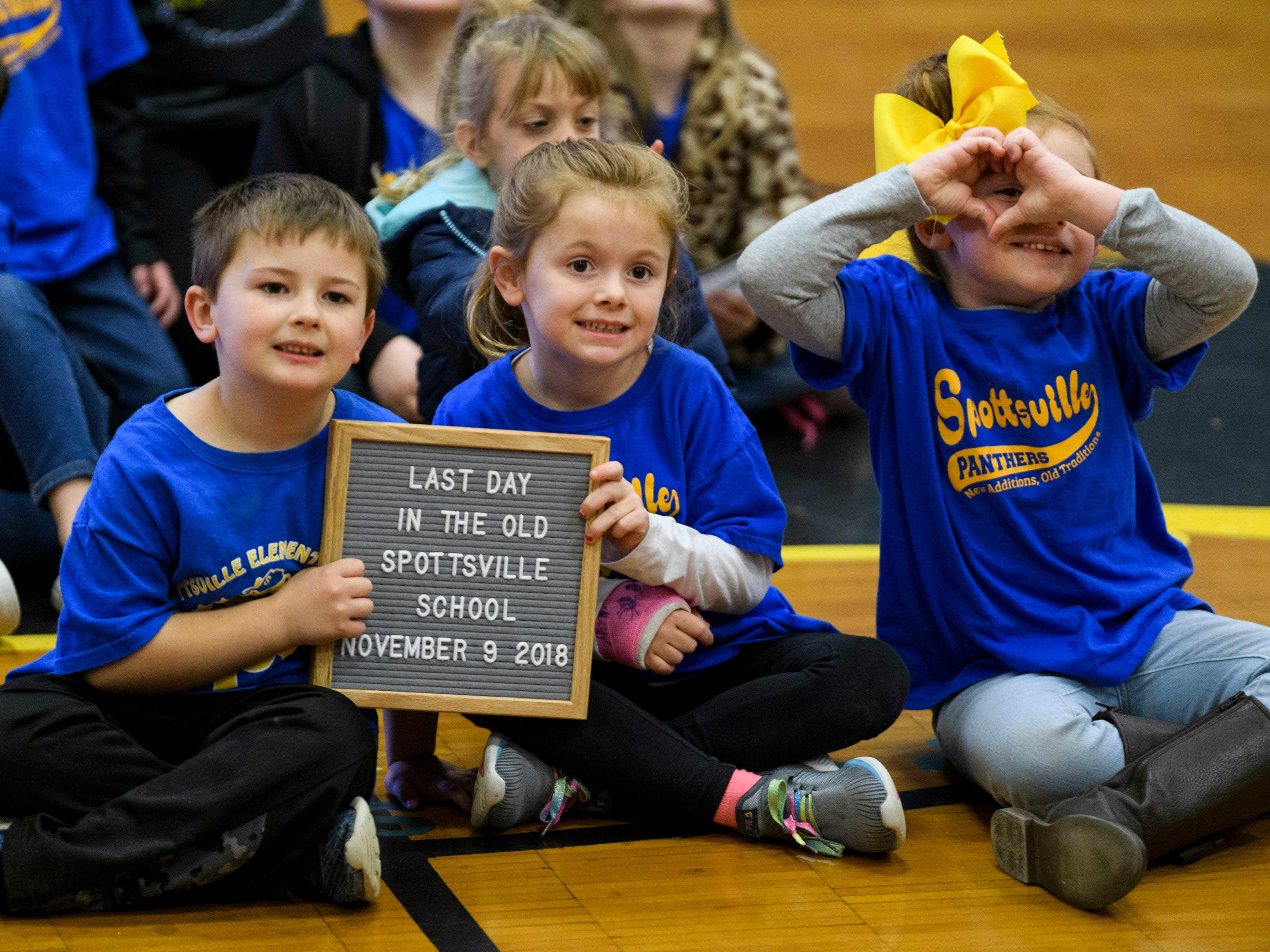 First-graders Jaxon Clark, from left, Laney Pike and Isabella Lane pose for a picture with their class inside the old Spottsville Elementary gymnasium to commemorate their last day of learning in the Henderson County school building, Friday, Nov. 9, 2018. They are scheduled to start classes in the new $17 million, 76,796-square-foot facility, which is located right beside the old building, Monday morning, November 12.