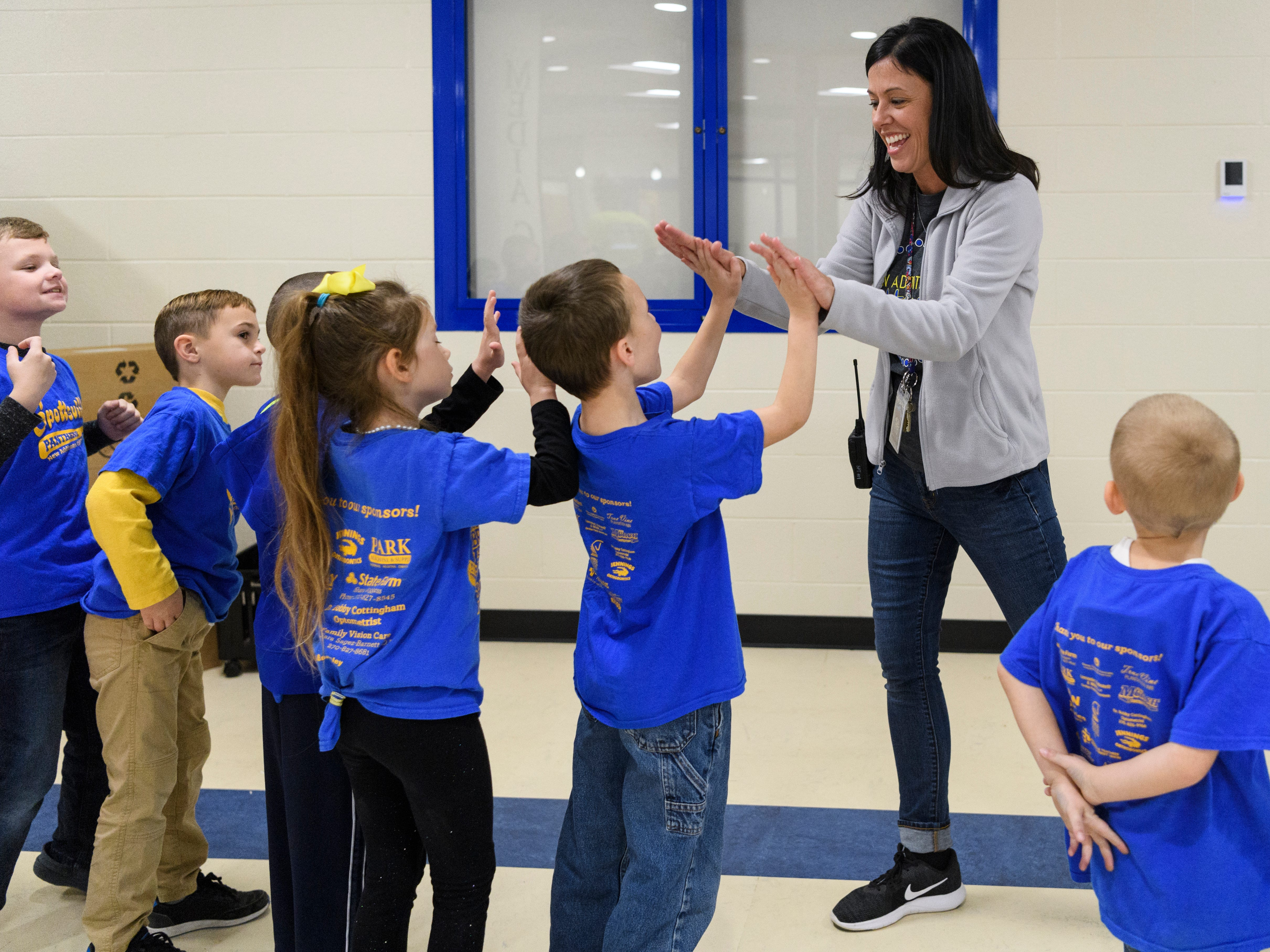 Principal Sarah Estabrook gives out high-fives and asks students if they are excited to move into the new Spottsville Elementary school building during a student transition tour of the new Henderson County public school facility, Friday morning, Nov. 9, 2018. All the students got to bring a few items over to their new classrooms and tour the building in preparation for their official move-in day, Monday, November 12.