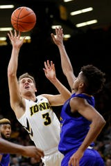 Iowa guard Jordan Bohannon drives to the basket over UKMC guard Rob Whitfield, right, during the first half Thursday.