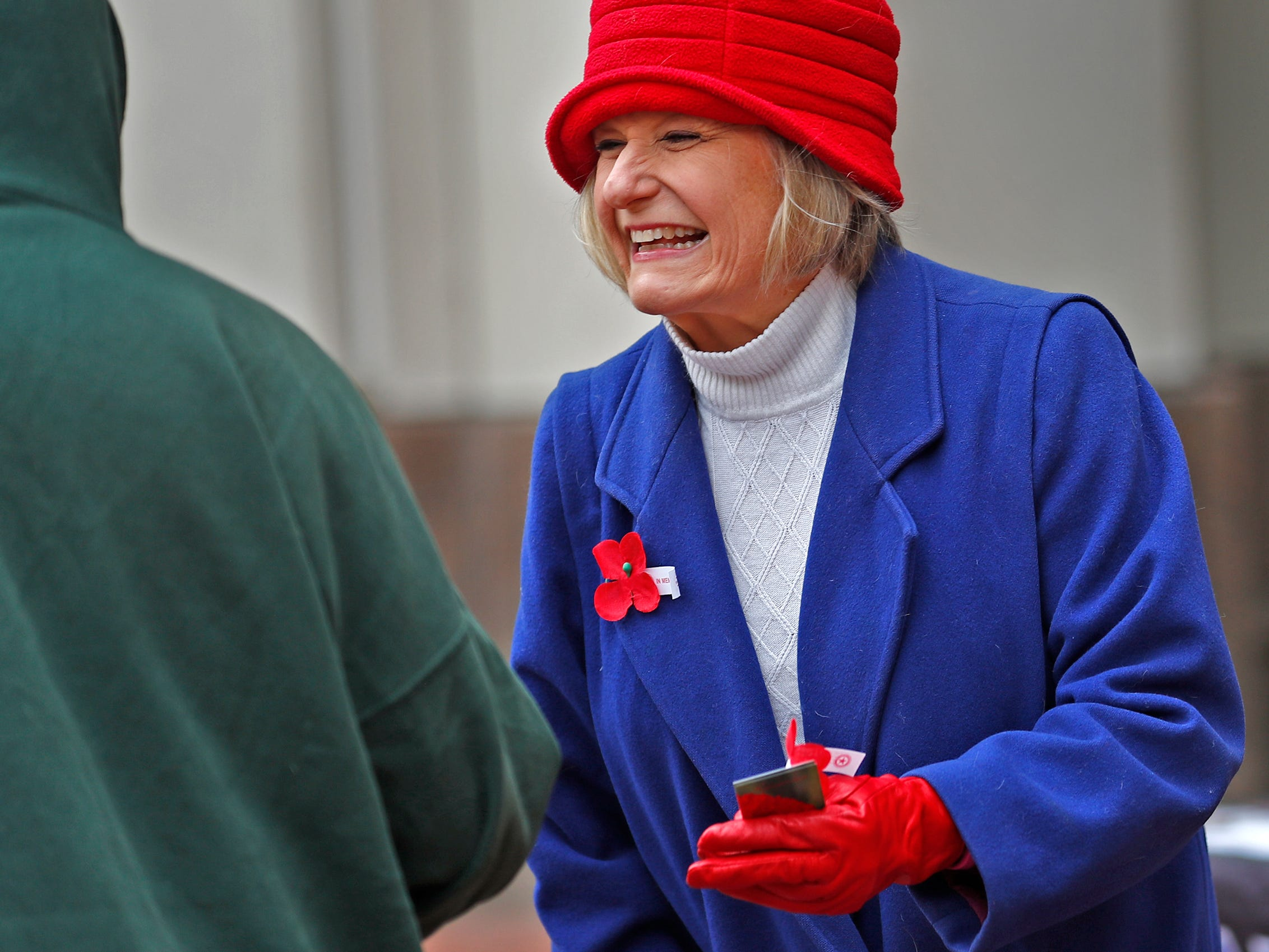 Marie Beason, Executive Director of the Indiana War Memorials Foundation, smiles as she gives away free Remembrance Poppies from the Indiana War Memorials Foundation (IWMF) and Emmis Communications, on Monument Circle, Friday, Nov. 9, 2018.  The flower give-away is in celebration of Veterans Day and the 100th anniversary of the end of World War I.