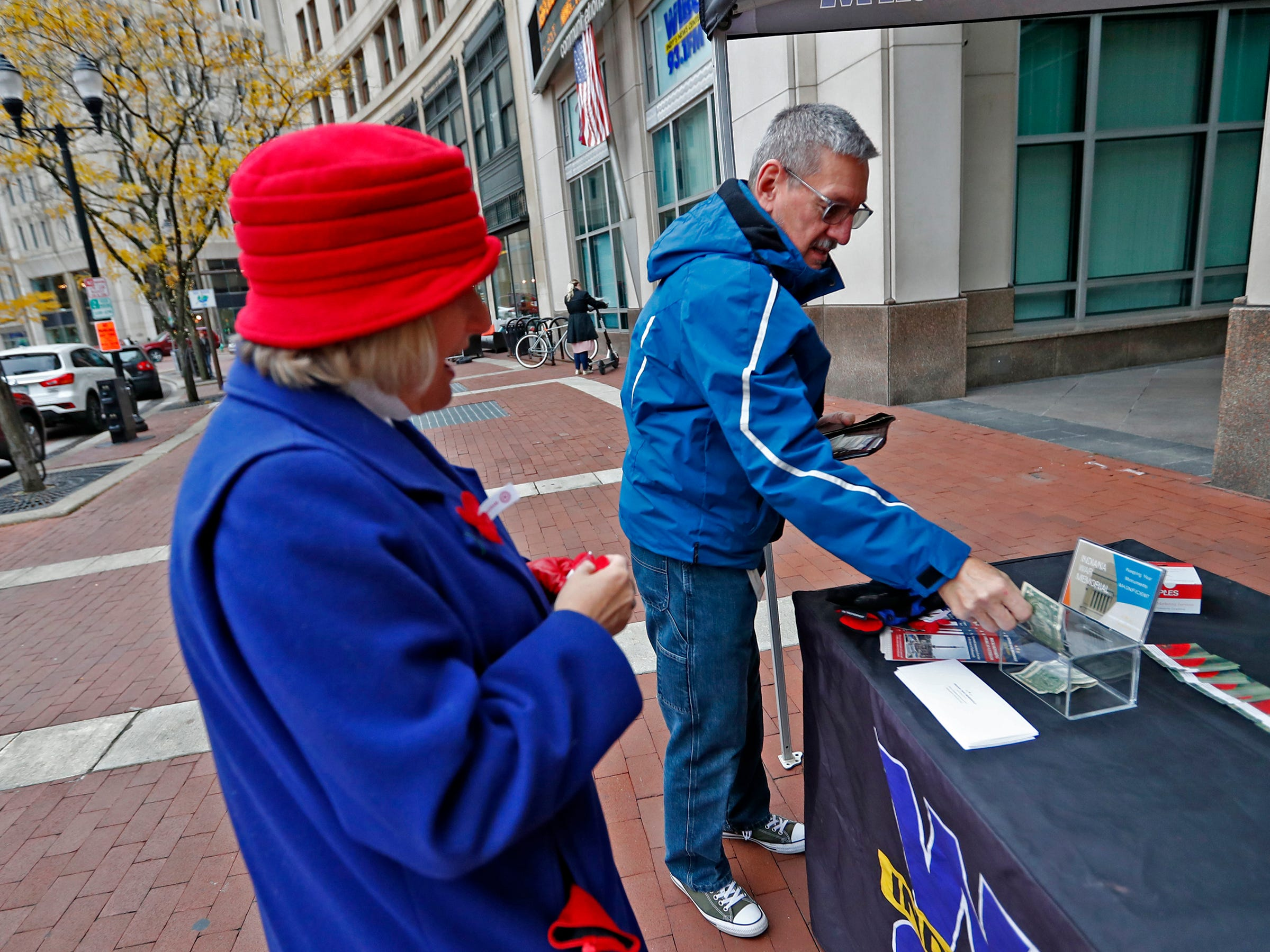 Bill Carlson, right, makes a donation after Marie Beason, Executive Director of the Indiana War Memorials Foundation, gave him a free Remembrance Poppy from the Indiana War Memorials Foundation (IWMF) and Emmis Communications, on Monument Circle, Friday, Nov. 9, 2018.  The flower give-away is in celebration of Veterans Day and the 100th anniversary of the end of World War I.