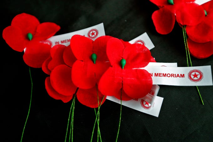 Free Remembrance Poppies sit ready to be given away from the Indiana War Memorials Foundation (IWMF) and Emmis Communications, on Monument Circle, Friday, Nov. 9, 2018.  The flower give-away is in celebration of Veterans Day and the 100th anniversary of the end of World War I.