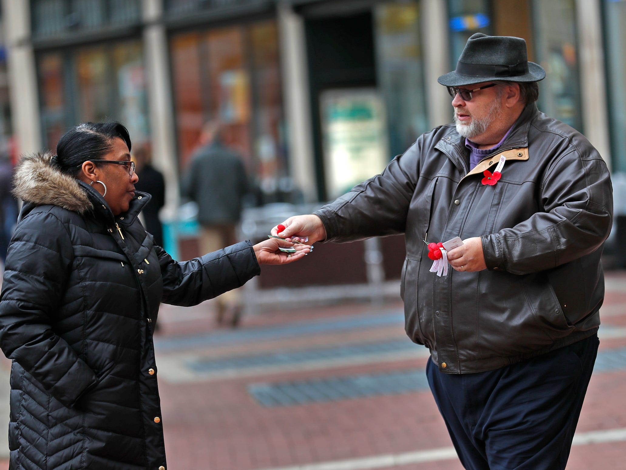 Michael Beason gives away free Remembrance Poppies from the Indiana War Memorials Foundation (IWMF) and Emmis Communications, on Monument Circle, Friday, Nov. 9, 2018.  The flower give-away is in celebration of Veterans Day and the 100th anniversary of the end of World War I.