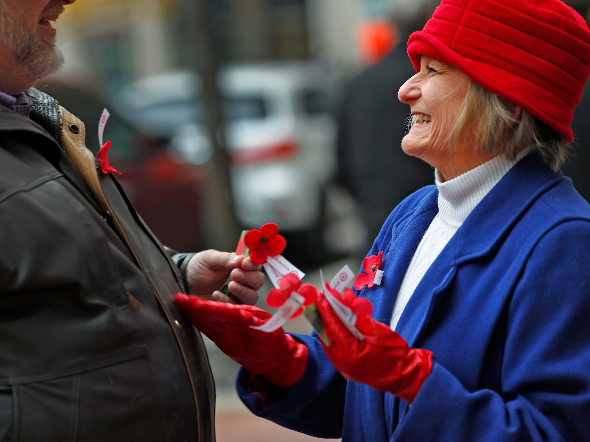 Marie Beason, Executive Director of the Indiana War Memorials Foundation, right, smiles with her husband Michael Beason, left, as they give away free Remembrance Poppies from the Indiana War Memorials Foundation (IWMF) and Emmis Communications, on Monument Circle, Friday, Nov. 9, 2018.  The flower give-away is in celebration of Veterans Day and the 100th anniversary of the end of World War I.