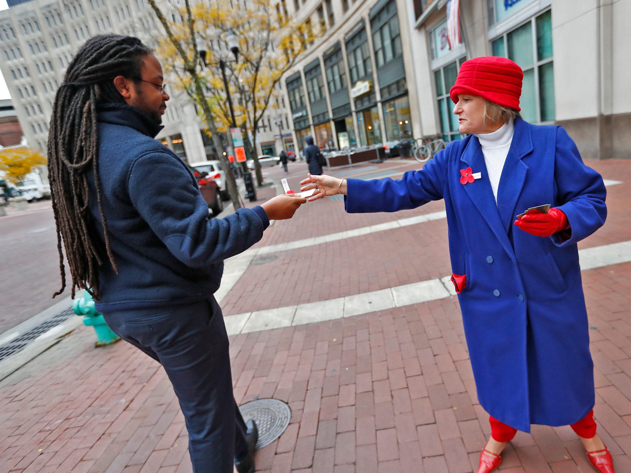 Marie Beason, Executive Director of the Indiana War Memorials Foundation, right, as she gives away free Remembrance Poppies from the Indiana War Memorials Foundation (IWMF) and Emmis Communications, on Monument Circle, Friday, Nov. 9, 2018.  The flower give-away is in celebration of Veterans Day and the 100th anniversary of the end of World War I.