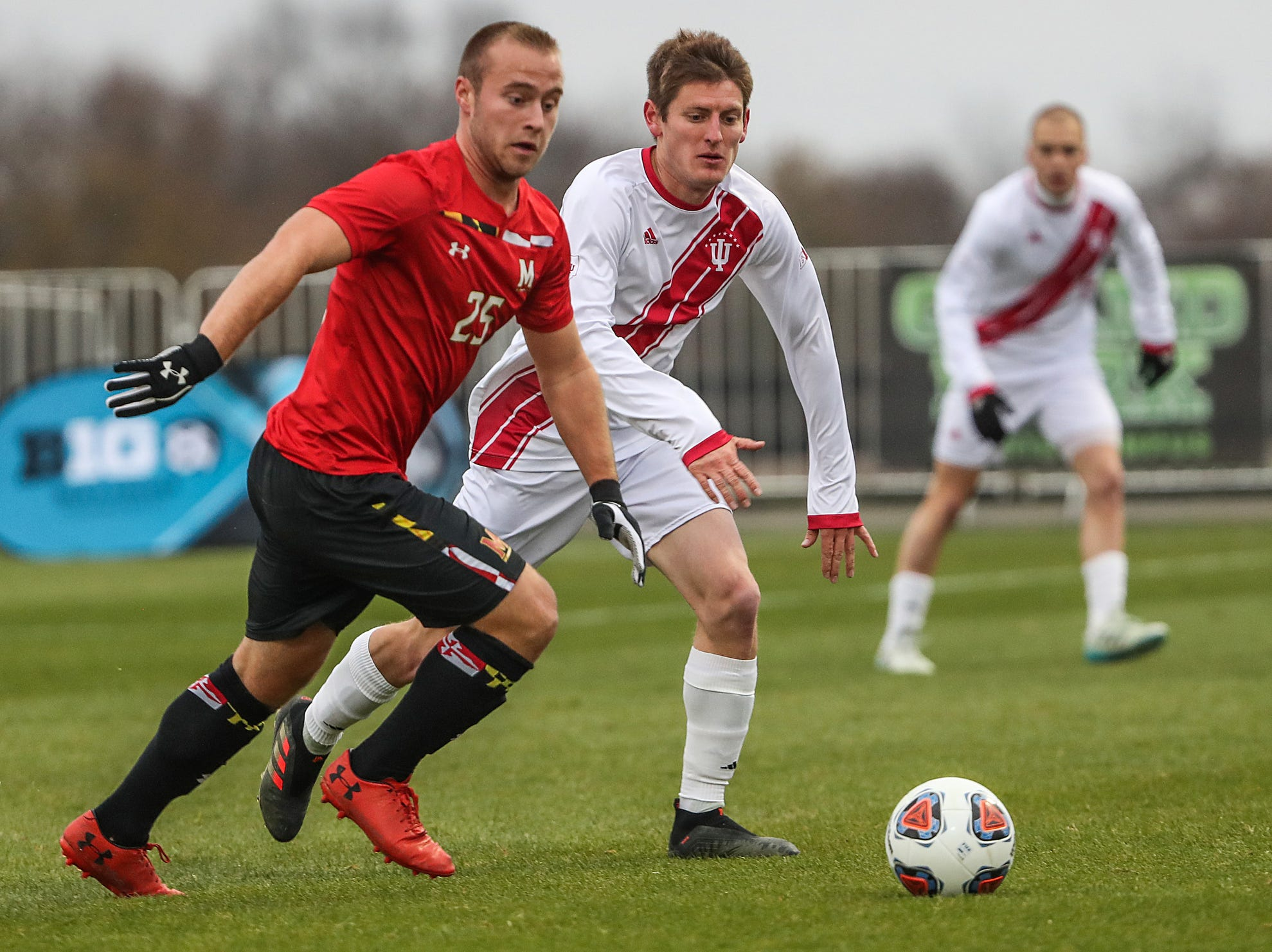 Maryland Terrapins defender Ben Di Rosa (25) moves the ball as Indiana Hoosiers Trevor Swartz (7) approaches from behind during the first half of Big Ten semifinals at Grand Park in Westfield, Ind., Friday, Nov. 9, 2018. Indiana and Maryland tied 1-1, with the Hoosiers advancing in penalty kicks, 4-3.