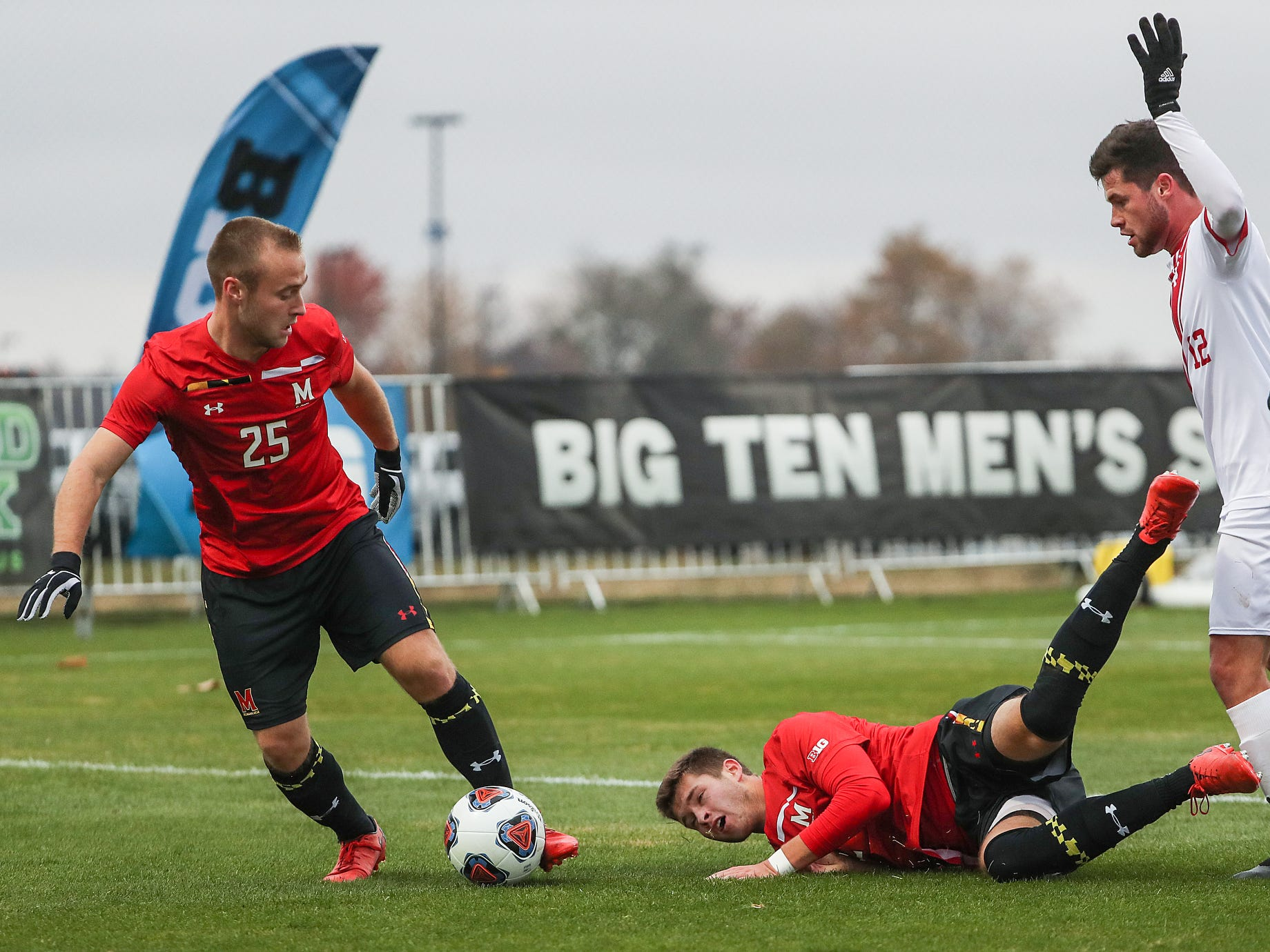 From left, Maryland Terrapins defender Ben Di Rosa (25) takes over possession as Brett St. Martin (12) hits the ground after tangling with Indiana Hoosiers Austin Panchot (12) during the first half of Big Ten semifinals at Grand Park in Westfield, Ind., Friday, Nov. 9, 2018. Indiana and Maryland tied 1-1, with the Hoosiers advancing in penalty kicks, 4-3.