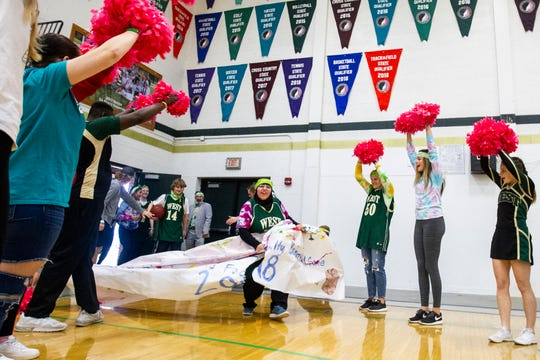 Iowa City West senior Hafiza El-Zein (54) breaks through a banner while players are introduced before a basketball game on Thursday, Nov. 1, 2018, at West High School in Iowa City.