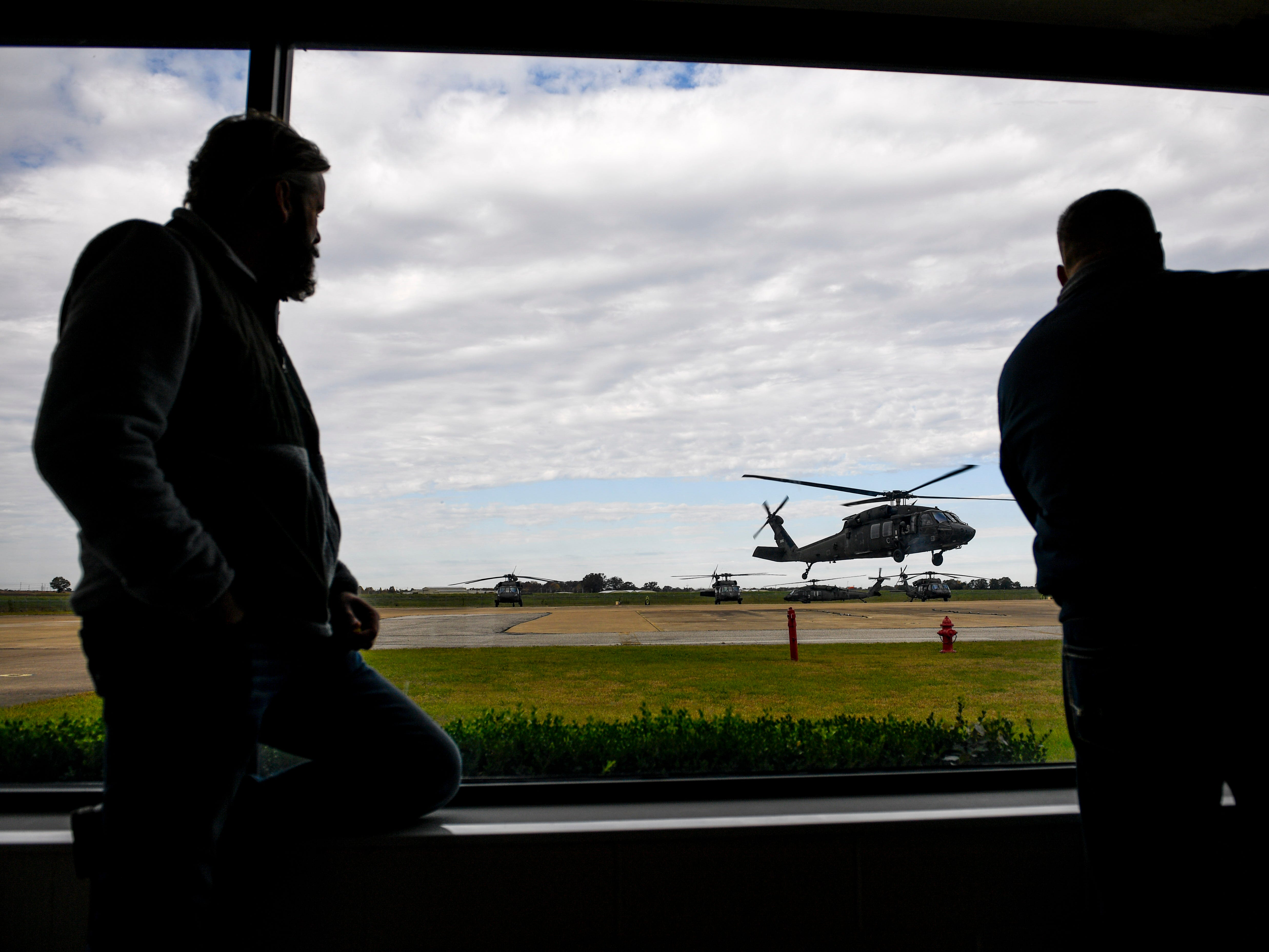 Attendees look out the windows of a building at National Guardsmen testing their helicopters during the annual Bosslift event put on by Employer Support of the Guard and Reserve (ESGR) and the Tennessee National Guard at Army Aviation Facility in Jackson, Tenn., on Thursday, Nov. 8, 2018.