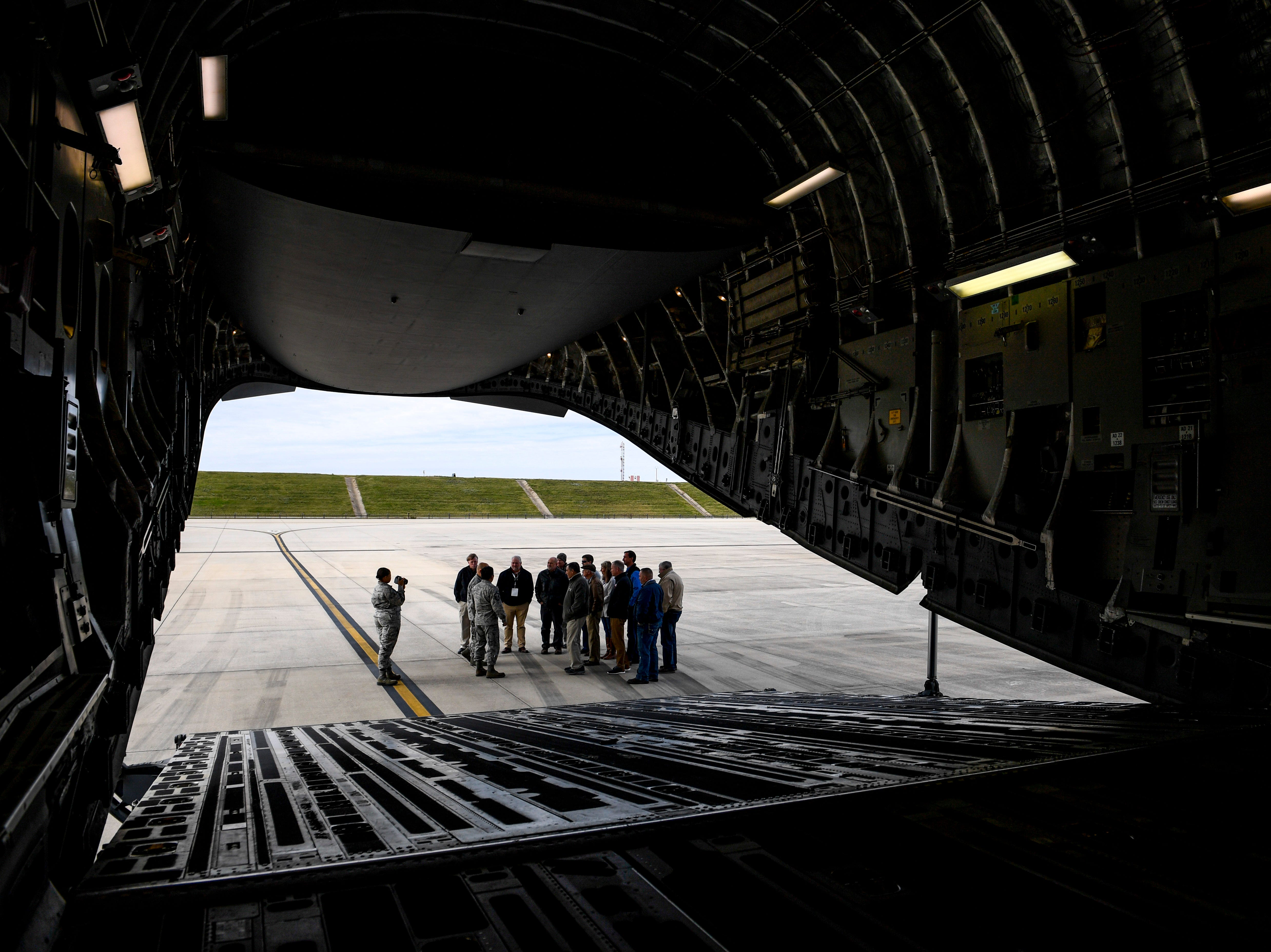 Attendees stand and chat with a National Guardsmen outside the rear of a C-17 during the annual Bosslift event put on by Employer Support of the Guard and Reserve (ESGR) and the Tennessee National Guard at 164th Airlift Wing in Memphis, Tenn., on Thursday, Nov. 8, 2018.