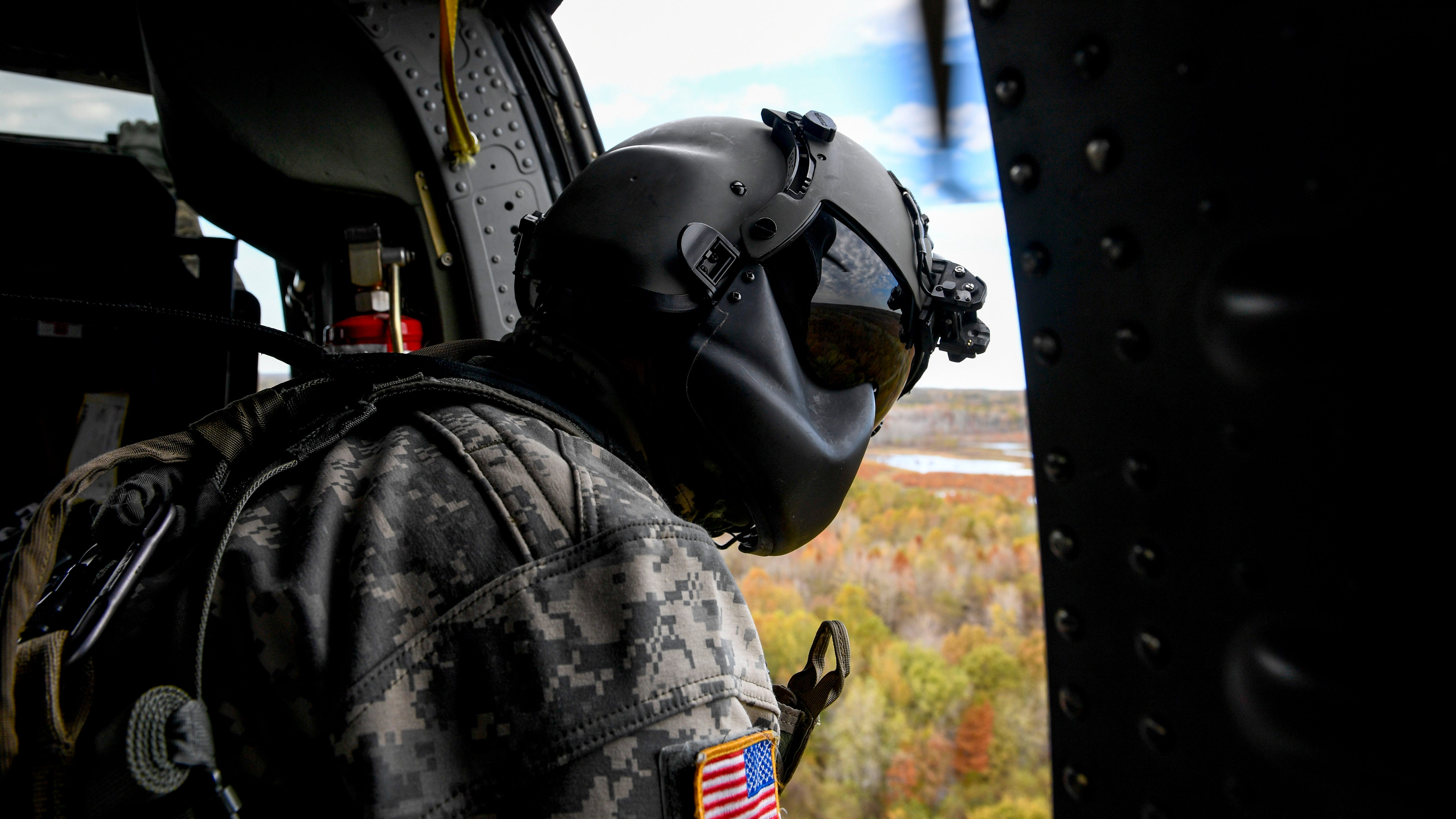 A National Guardsmen leans out the window of a helicopter during the annual Bosslift event put on by Employer Support of the Guard and Reserve (ESGR) and the Tennessee National Guard at Army Aviation Facility in Jackson, Tenn., on Thursday, Nov. 8, 2018.