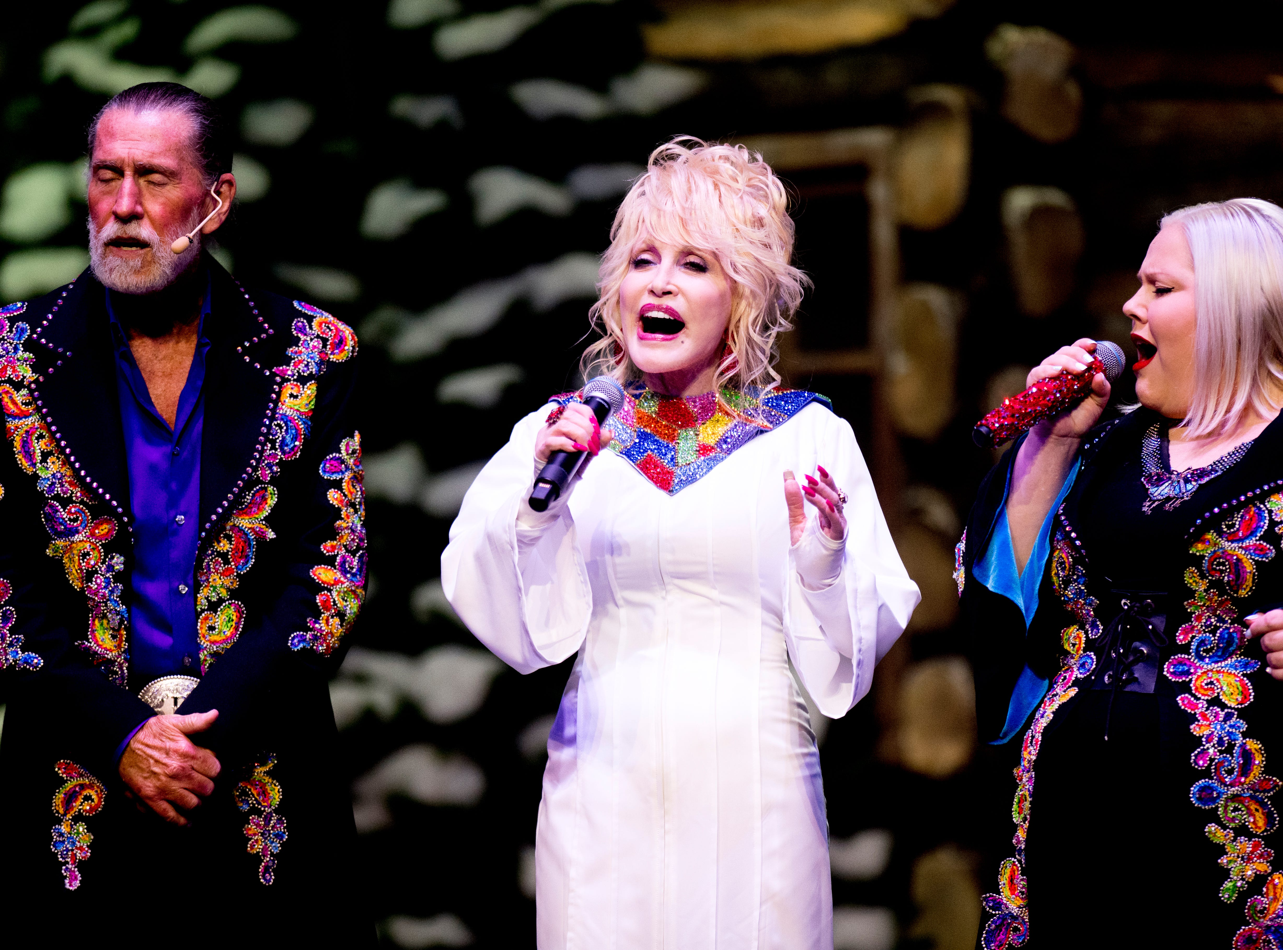Dolly Parton and her brother Randy Parton, left, and her niece Heidi Parton, right, sing during the Christmas in the Smokies show at Dollywood in Pigeon Forge, Tennessee on Friday, November 9, 2018. Glacier Ridge features several new lighting displays, including a 50-ft. tall animated tree, the all new Arctic Passage and the Northern Lights.