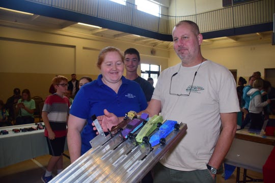 Ken Wise, (right) Boy Scout Den Leader, lends a helping hand to Jennifer Warren, Girl Scout Troop 20496 to start a race at the Girl Scout Daisy Derby held at Beaver Ridge United Methodist Church Saturday, Nov. 3.