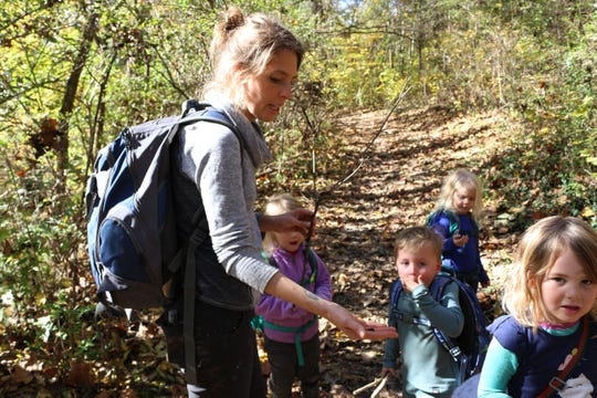 Knox Forest School director Sara Otis stops to examine a jelly mushroom with her students.