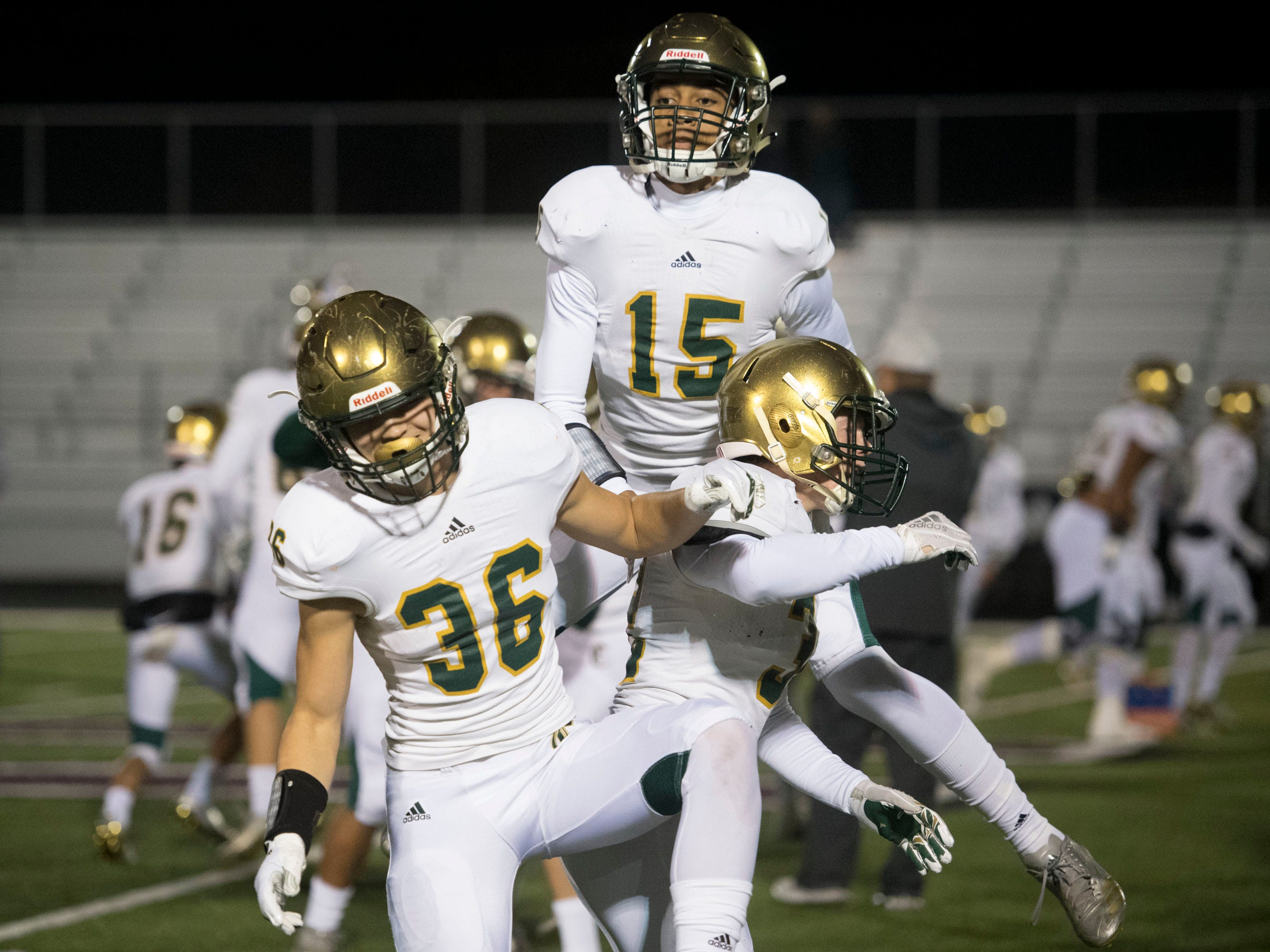Knoxville Catholic's Zachary Shannon (36), Spencer Margolis (32), and Raaphell Mayes (15) celebrate before the start of the second round playoff against Fulton on Friday, November 9, 2018.