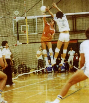 Earl Sharpe, in orange, spikes the ball off a Chuck House block in this undated photo.