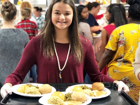 Eighth-grader Sarah Verneuli serves a baked dinner at the Gresham Middle School Veterans Day Assembly on Nov. 9, 2018.