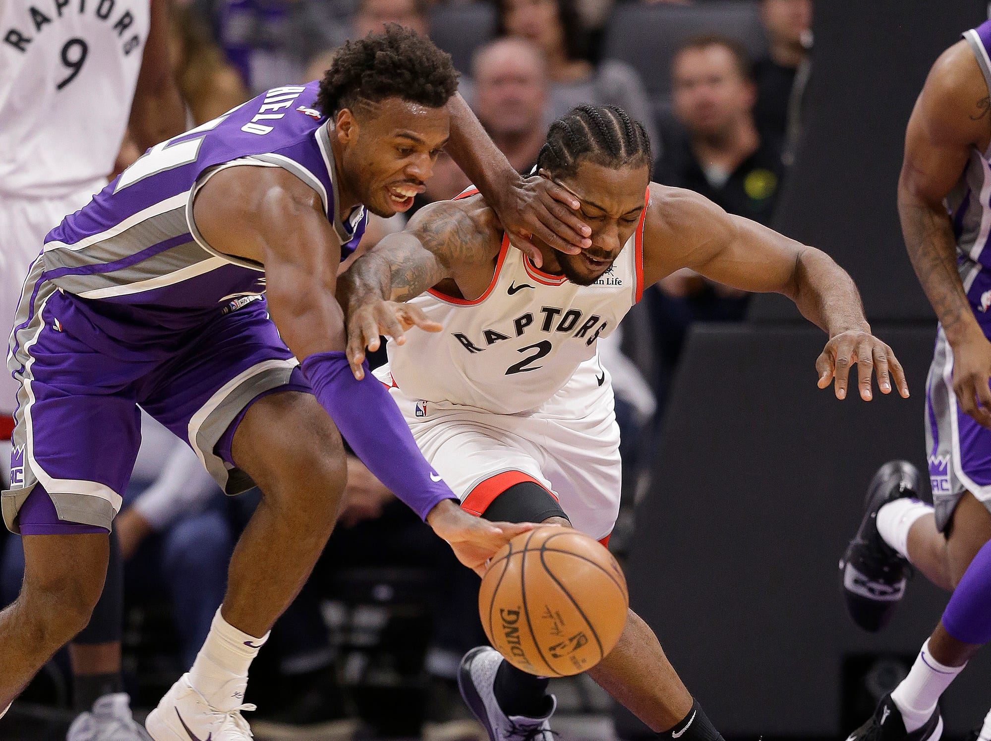 Sacramento Kings guard Buddy Hield, left, and Toronto Raptors forward Kawhi Leonard scramble for the ball during the second half of an NBA basketball game Wednesday, Nov. 7, 2018, in Sacramento, Calif. The Raptors won 114-105.  (AP Photo/Rich Pedroncelli)