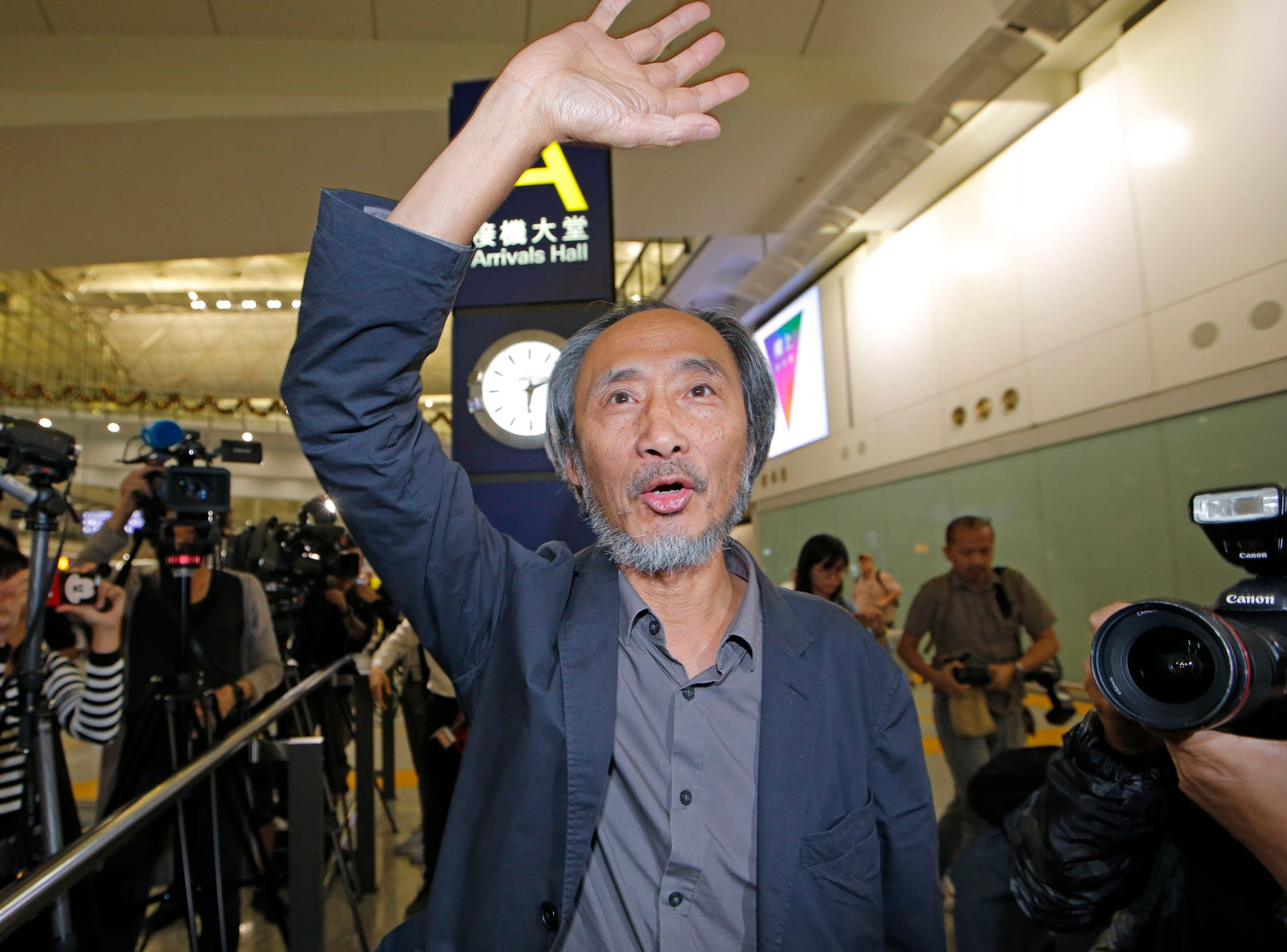 "Chinese dissident writer Ma Jian waves to media after arriving Hong Kong international airport, Friday, Nov. 9, 2018. Despite Mallet's rejection, Hong Kong on Friday permitted dissident writer Ma to enter to attend a literary festival, even after an arts venue in the city canceled his appearance. Ma, whose novels frequently satirize China's communist leaders, told reporters he experienced nothing unusual while passing through passport control and that organizers were still lining-up a place for him to speak. ""The lecture will definitely happen. If there is a single Hong Kong person who is willing to listen, or a single reader who contacts me, I will be there,"" Ma said. (AP Photo/Kin Cheung)"