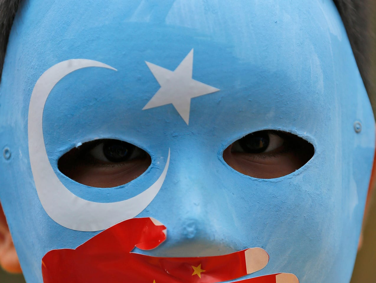 A child from the Uighur community living in Turkey wears a mask in the colours of the flag what ethnic Uighurs call 'East Turkestan', with a painted hand with the colours of China's flag, during a protest in Istanbul, Tuesday, Nov. 6, 2018, against what they allege is oppression by the Chinese government to Muslim Uighurs in the far-western Xinjiang province. (AP Photo/Lefteris Pitarakis)