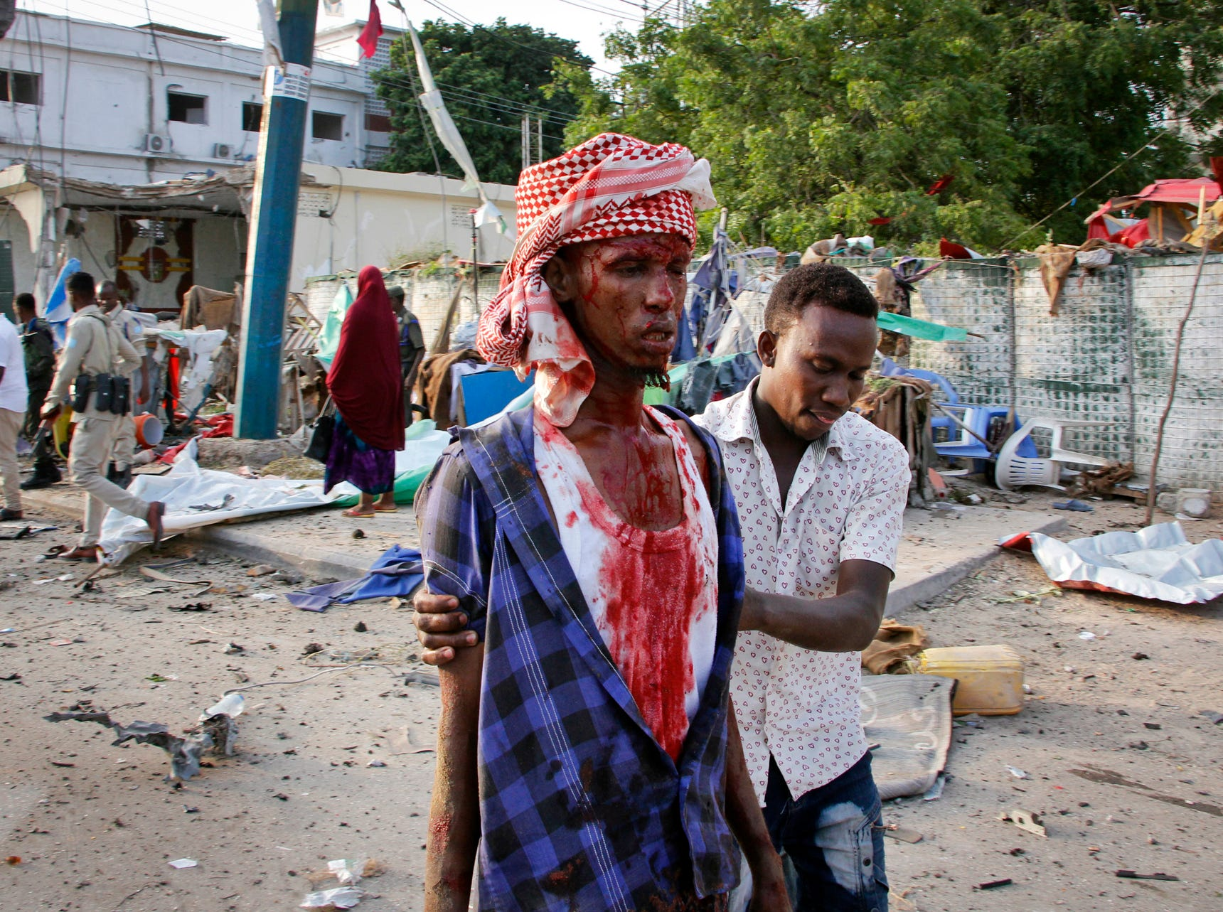 A Somali helps an injured civilian who was wounded in a bomb blast near the Sahafi hotel in the capital Mogadishu, Somalia, Friday, Nov. 9, 2018. Three car bombs by Islamic extremists exploded outside the hotel, which is located across the street from the police Criminal Investigations Department, killing at least 10 people according to police. (AP Photo/Farah Abdi Warsameh)