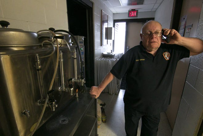 Fowlerville Fire Chief John Wright takes a phone call Friday, Nov. 9, 2018 in a hallway of the station that has turnout gear, folding chairs and a coffee maker.
