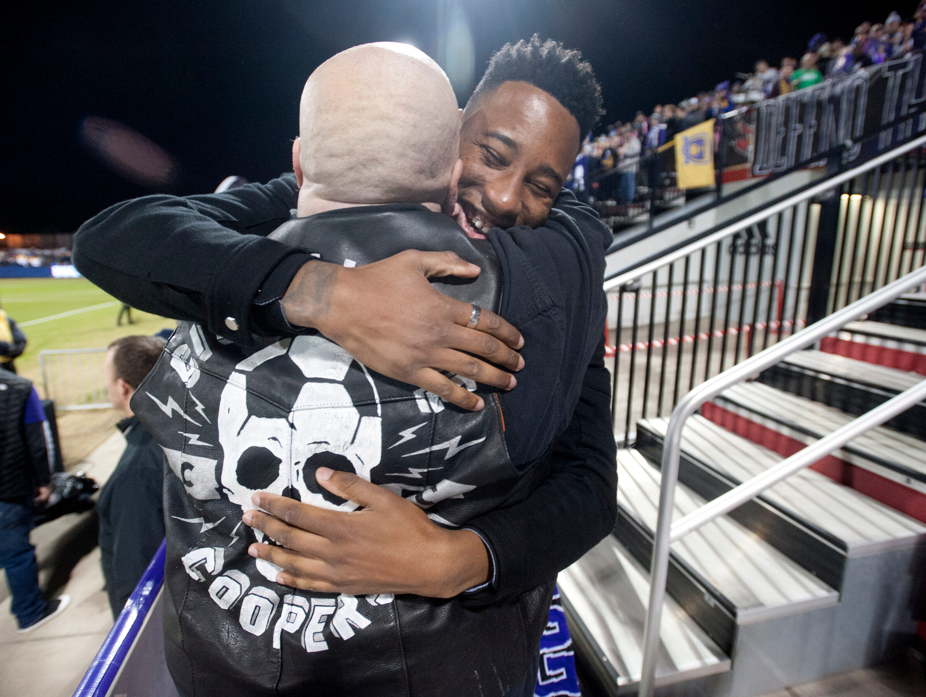 Mark Anthony Kaye of the Los Angeles FC, right, hugs Louisville Coopers' Joe Valla after Valla sang the National Anthen before the start of the  Louisville City FC-Phoenix Rising FC championship game for the 2018 USL Cup.November 08, 2018