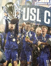 Louisville City FC's Magnus Rasmussen, left, Alexis Souahy, center and Niall McCabe, right, celebrate their team's back to back USL Cup defeating Phoenix Rising FC, 1-0.