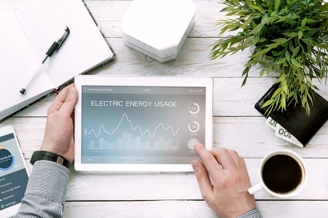 Man holds tablet pc with electric energy usage application made in graphic program.
