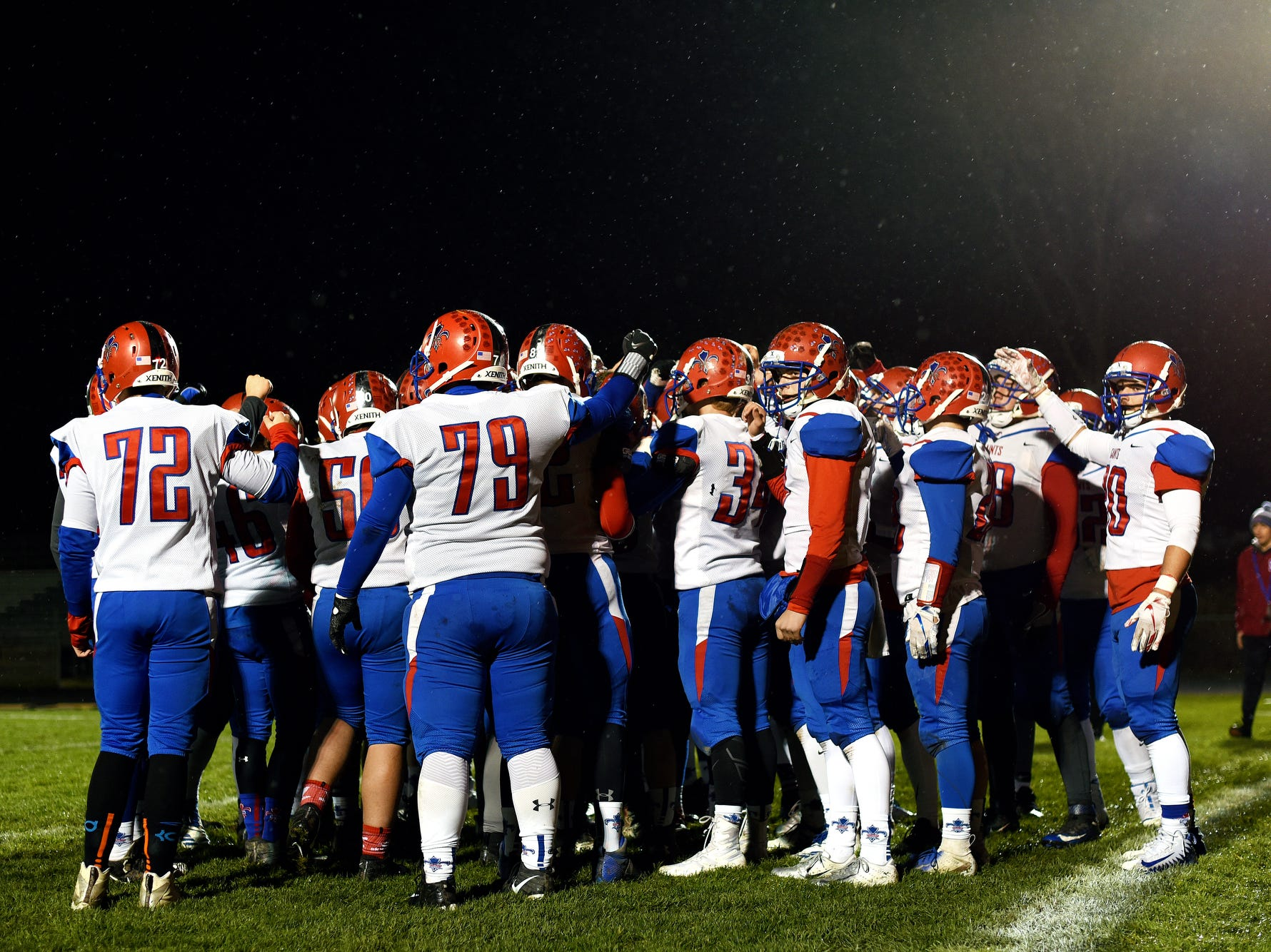 St. Clair huddles up while warming up before Saints game against Williamston on Friday, Nov. 9, 2018, in Williamston.