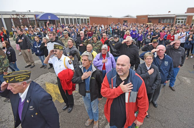 Students, staff and faculty of Lexington High School join members of the armed services singing the national anthem in the school's parking lot after honoring the servicemen and servicewomen with a program, songs and cheering them as they marched in the halls of the schools.