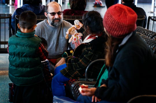 Local volunteer Lee Coleman offer toys to migrant children traveling from Dallas to Nashville during a stop at the Greyhound Bus Station on Airways Blvd.