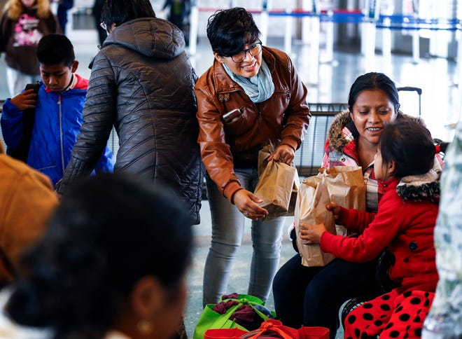 Local volunteer Iris Mercado offers food to asylum seekers during a stop at the Greyhound Bus Station on Airways last month.