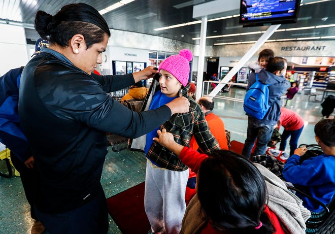 Local volunteer Jose Valverde (left) helps Naomi Garcia, 12, (middle) with a jacket at the Greyhound Bus Station on Airways Blvd. The girl, who is from Guatemala, was traveling with her family  to Nashville on Nov. 9, 2018.