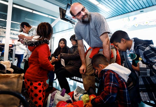 Local volunteer Lee Coleman offers toys to migrant children during a stop at the Greyhound Bus Station on Airways Blvd. in Memphis on Friday.