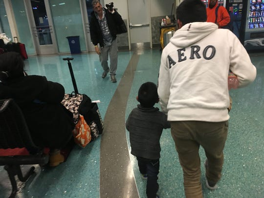 A Guatemalan man and child hustle to catch a bus at the Greyhound station near Memphis International Airport on Thursday, Nov. 11, 2018. They were part of a group of migrants that received help from a Memphis-area aid group.