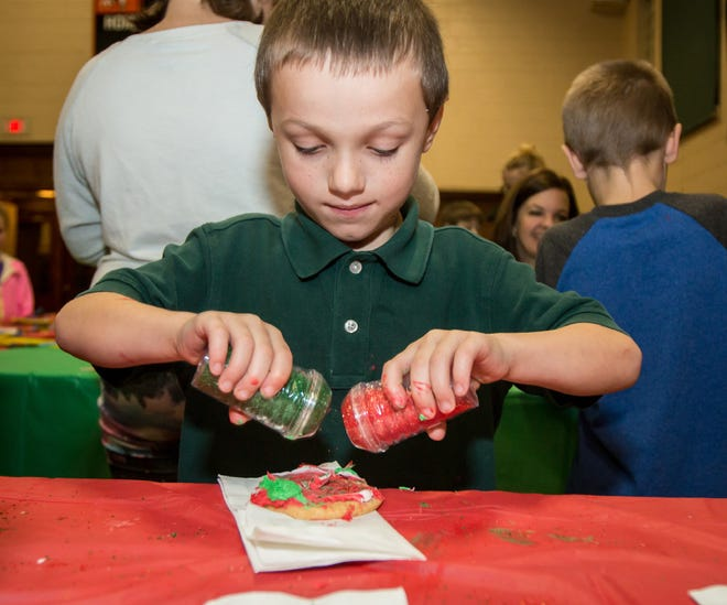 Ethan Gregory uses two hands decorating his Christmas cookie at the 2016 annual Christmas Tree Lighting.