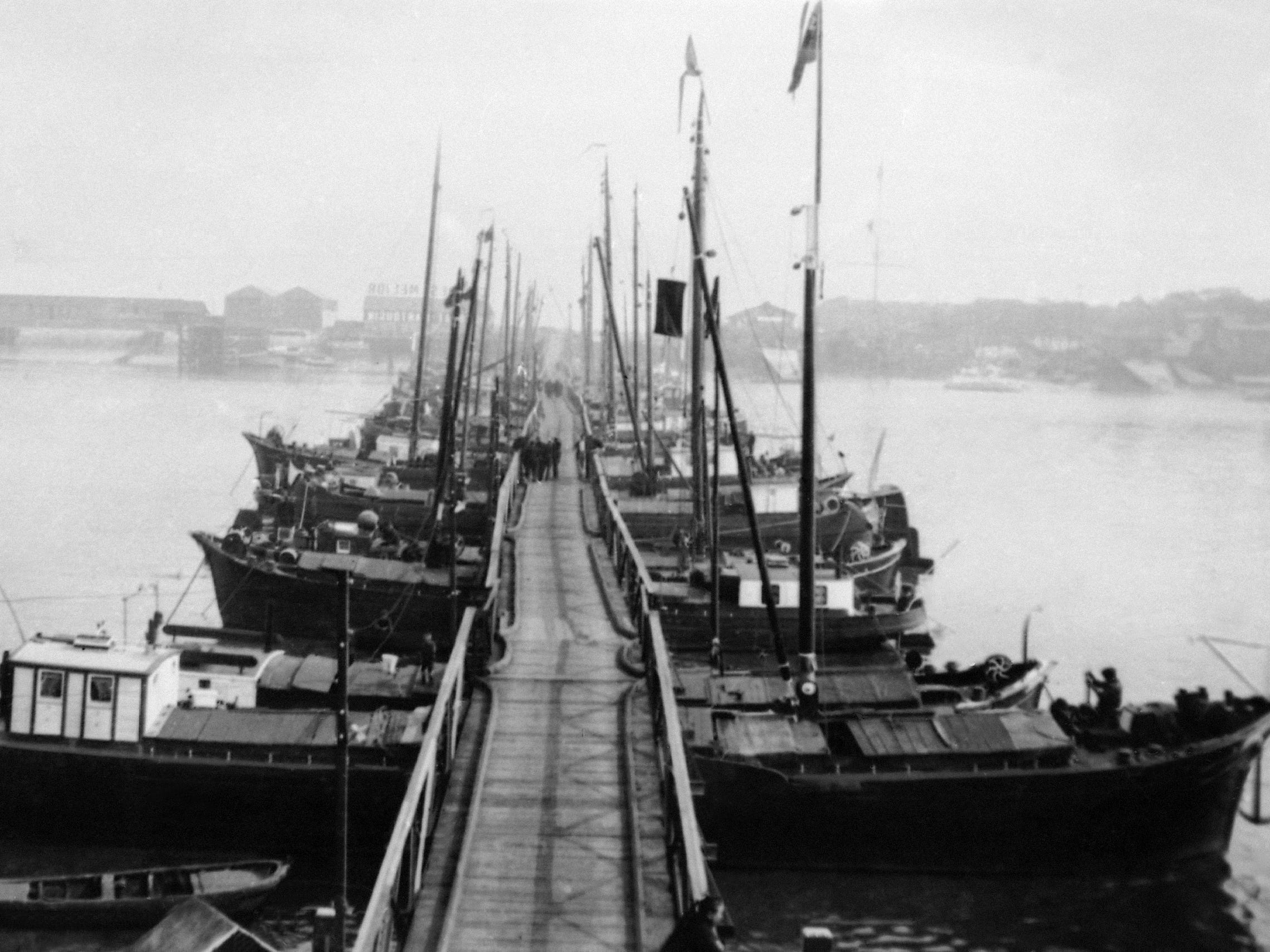 In this 1914 photo, small boats, pushed together, create a pontoon bridge over the Scheldt River in Antwerp, Belgium. The bridge was constructed during World War One for residents and troops to escape the German army.
