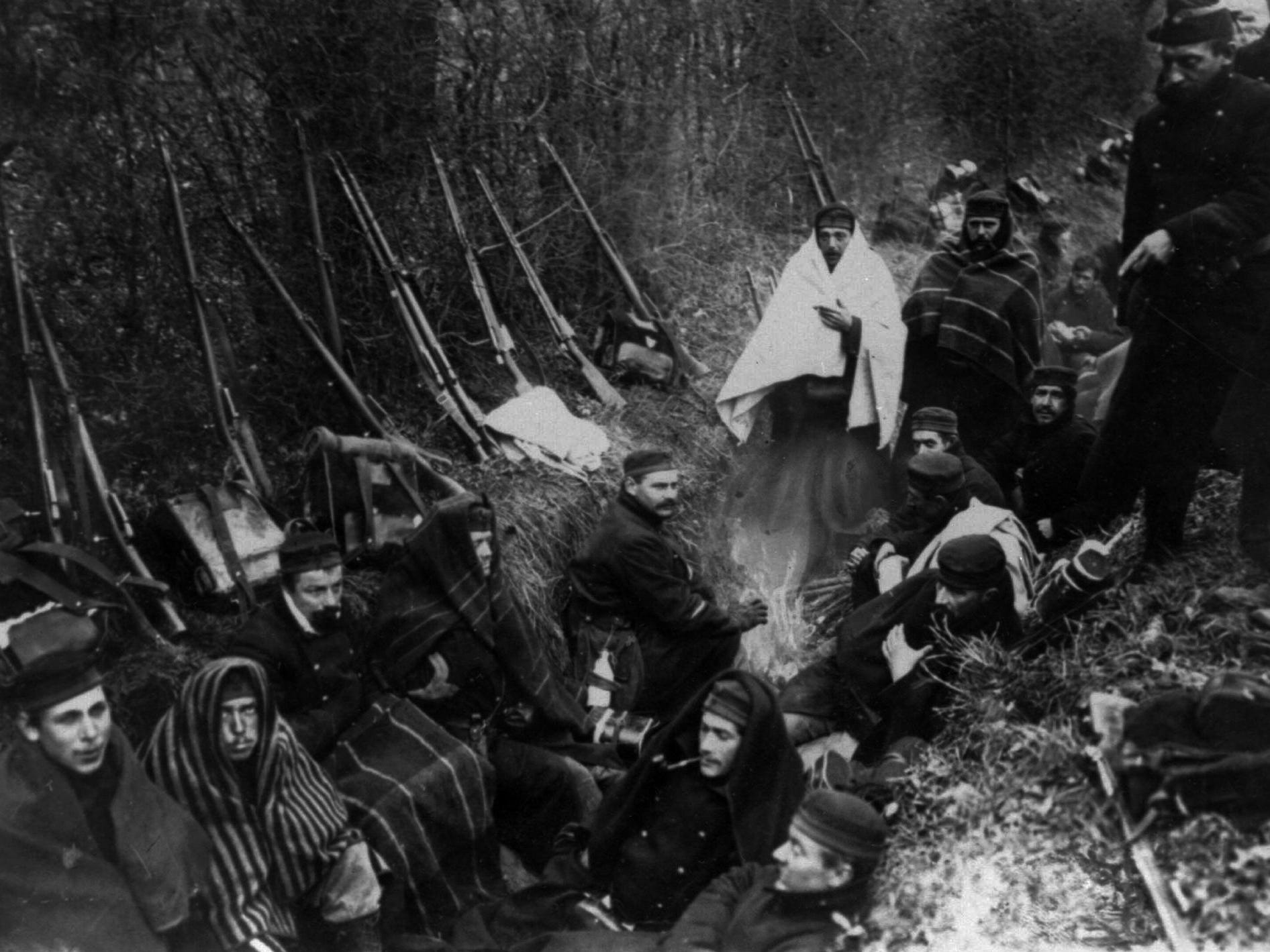 In this 1914 file photo, Allied troops huddle in a trench around a tiny fire near Ypres, Belgium.
