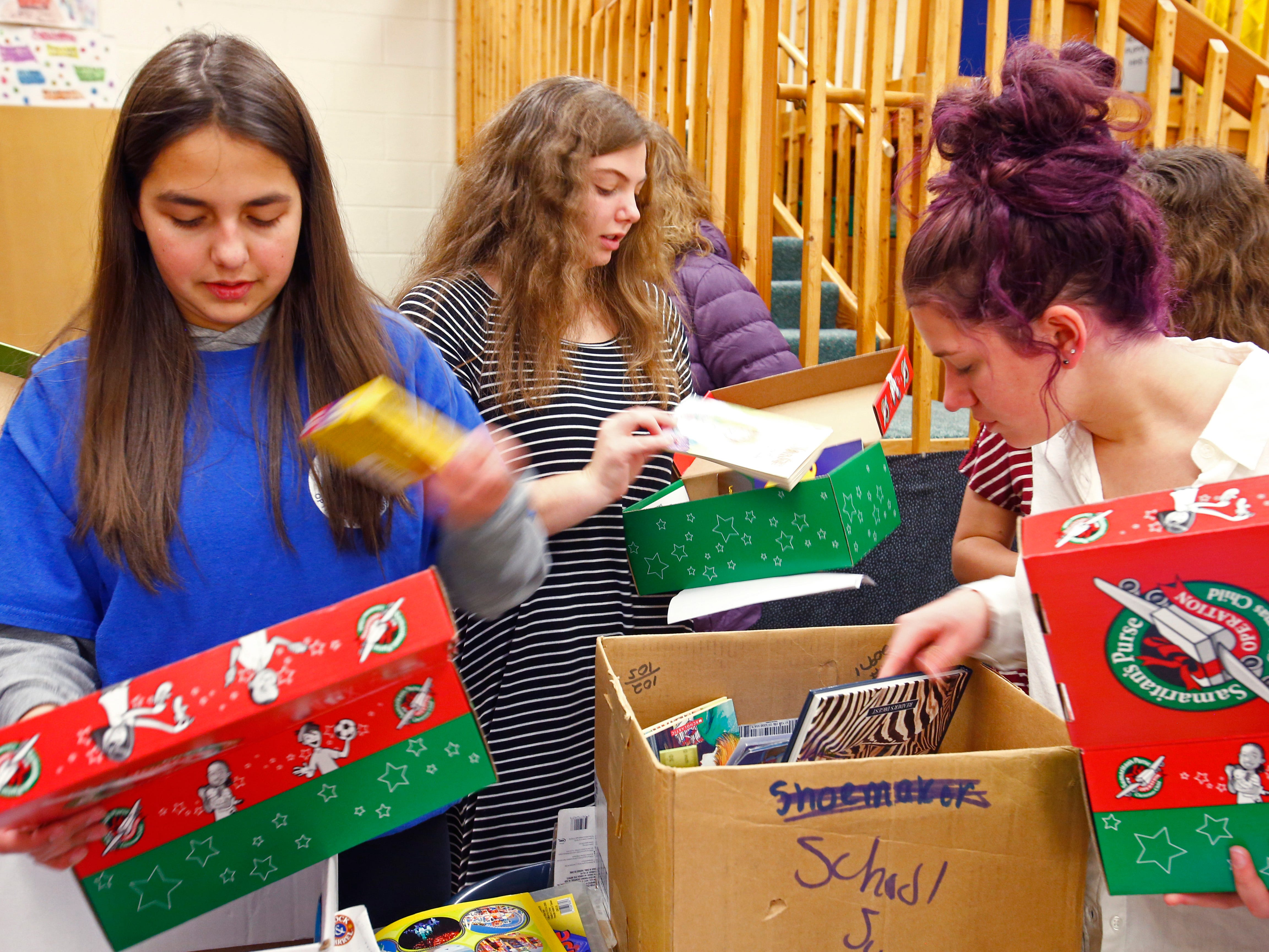 Sophomore Ashley Velasquez (left), Senior Molly Huberd and Junior Jenna Withrow pick items to pack into boxes for the Samaritan's Purse Operation Christmas Child project. Huberd organized the project for members of the Sussex Hamilton Junior Optimist International club to pack shoebox-sized containers with toys, clothing, personal care and other items on Nov. 7 as part of a service project with the Sussex/Lisbon/Lannon Optimist Club.