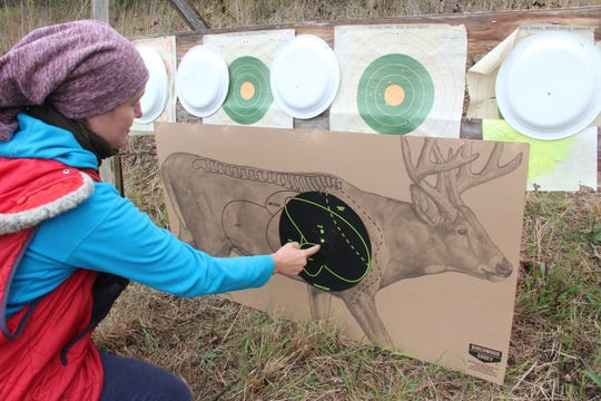 A hunter inspects a target during a rifle sight-in session.