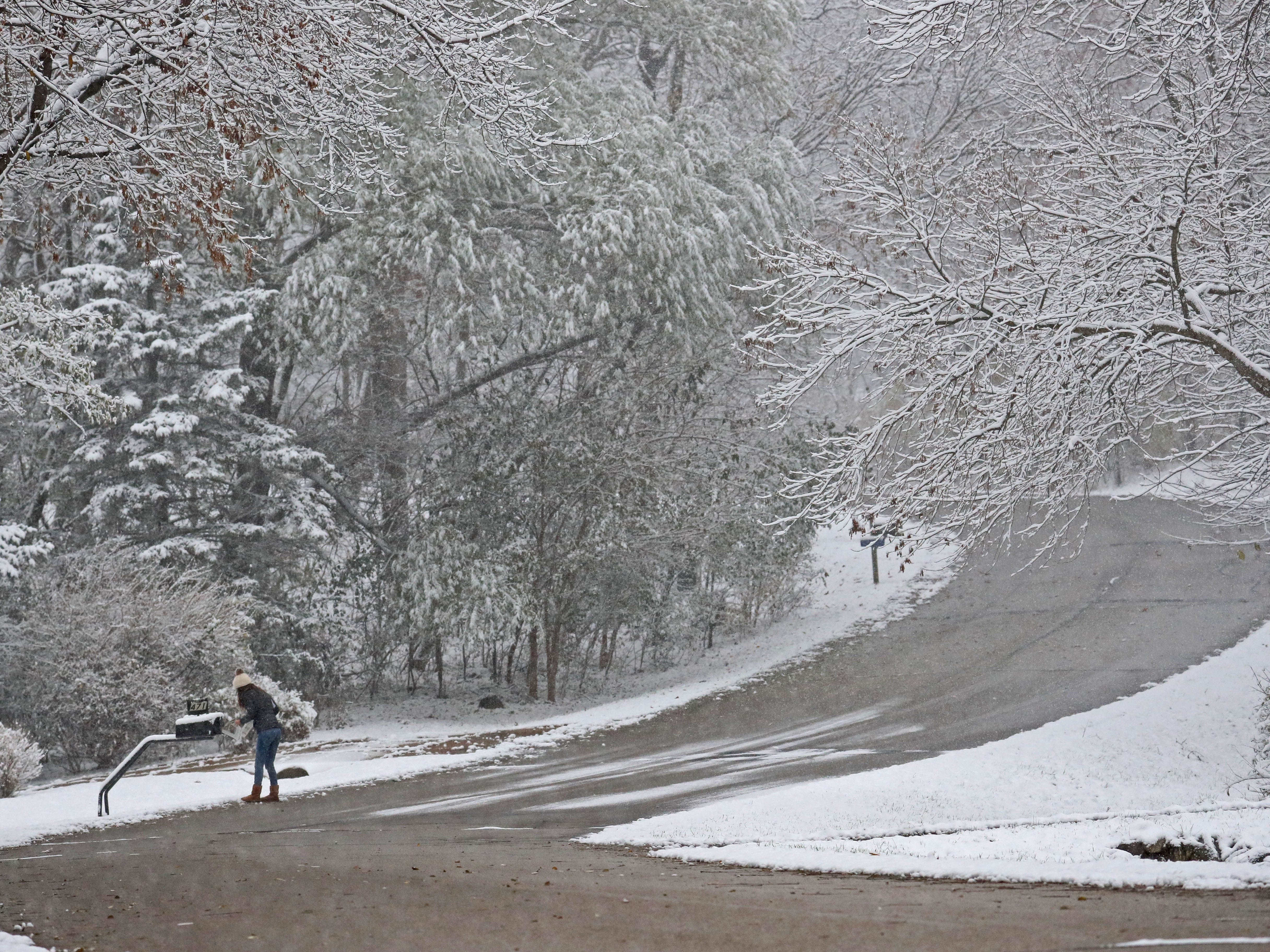 A woman is surrounded by the return of winter as she checks her mailbox on Garrison Court in Delafield.