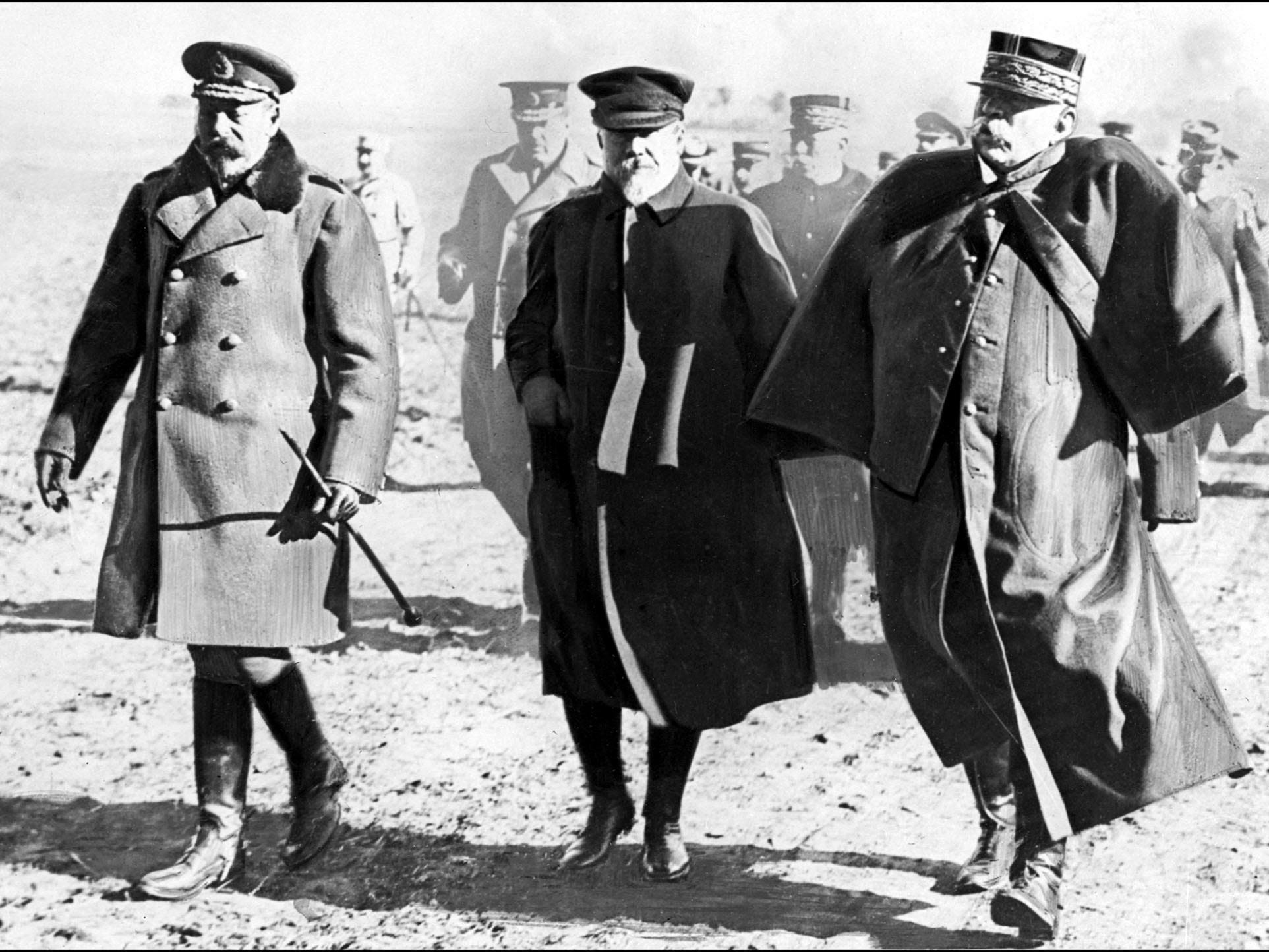 In this undated photo taken in 1915, King George V of Great-Britain (left to right), French President Raymond Poincare and French Marshal Joseph Joffre walk a battlefield the during WWI.